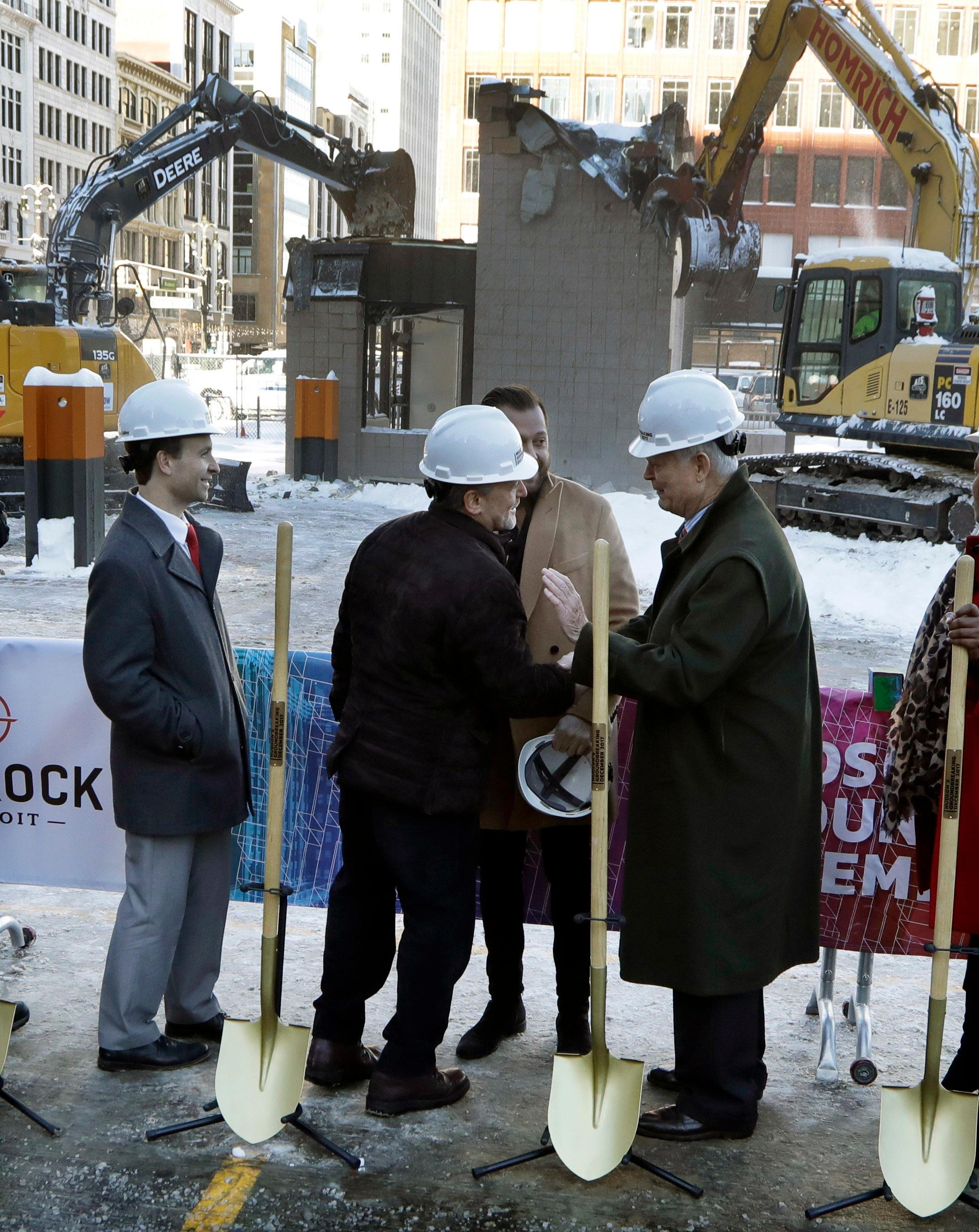 Quicken Loans founder Dan Gilbert, center, meets with Joe Hudson, former CEO of the J.L. Hudson Company at the groundbreaking site of the city's new 800-foot-tall building, Thursday, Dec. 14, 2017, in Detroit. Bedrock Detroit real estate says the $900 million two-building project will include a 58-story residential tower and 12-floor building for retail and conference space. The tower will have an 800-foot-tall (244-meter) sky deck.(AP Photo/Carlos Osorio)
