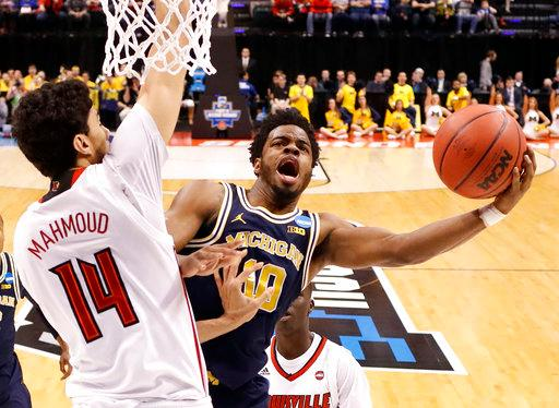 Michigan's Derrick Walton Jr. (10) shoots as Louisville's Anas Mahmoud (14) defends during the first half of a second-round game in the men's NCAA college basketball tournament Sunday, March 19, 2017, in Indianapolis. (AP Photo/Jeff Roberson)