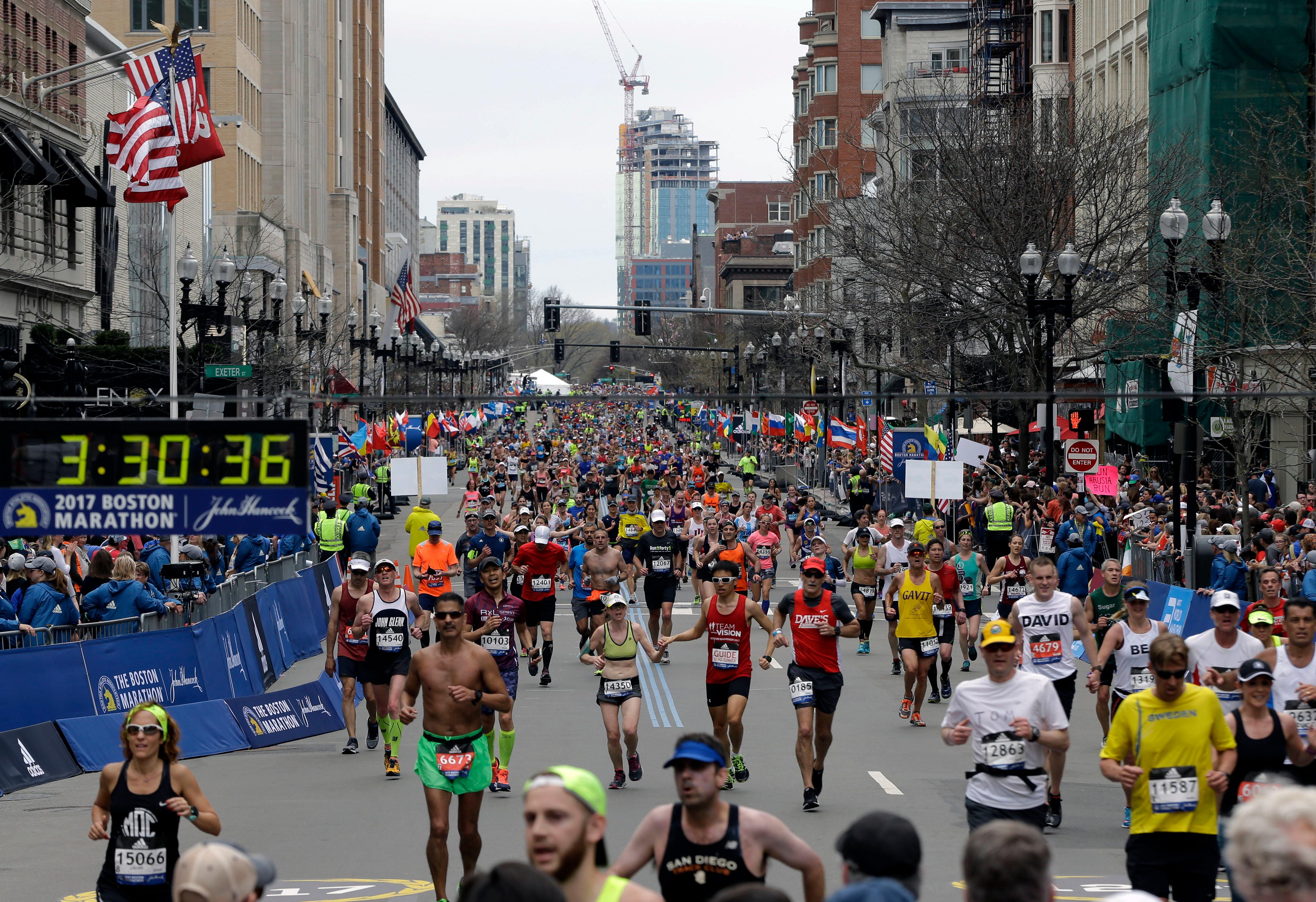 FILE - In this Monday, April 17, 2017, file photo, runners head to the finish line in the 121st Boston Marathon in Boston. (AP Photo/Elise Amendola, File)