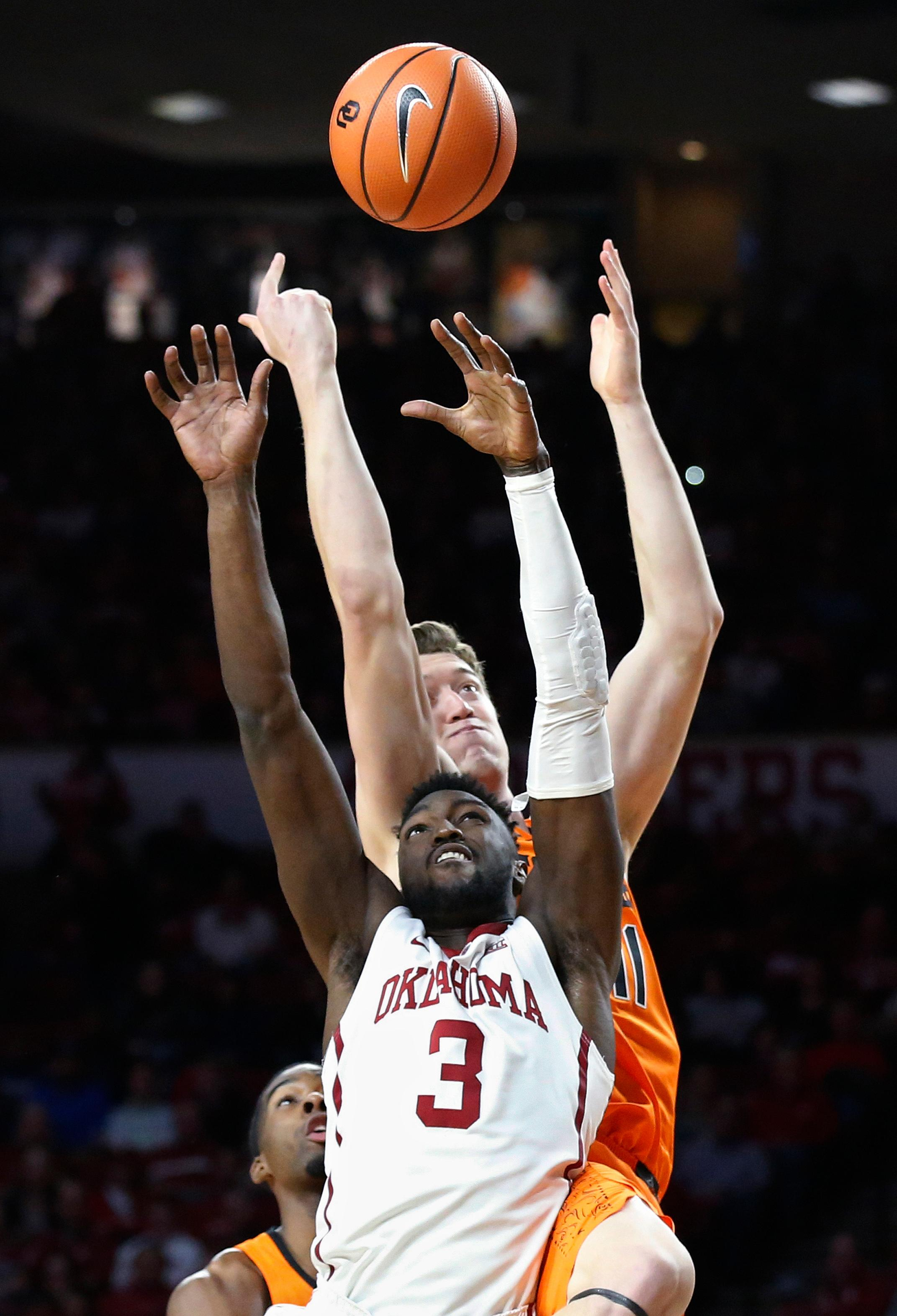 Oklahoma forward Khadeem Lattin (3) reaches for a rebound with Oklahoma State forward Mitchell Solomon, rear, during the first half of an NCAA college basketball game in Norman, Okla., Wednesday, Jan. 3, 2018. (AP Photo/Sue Ogrocki)