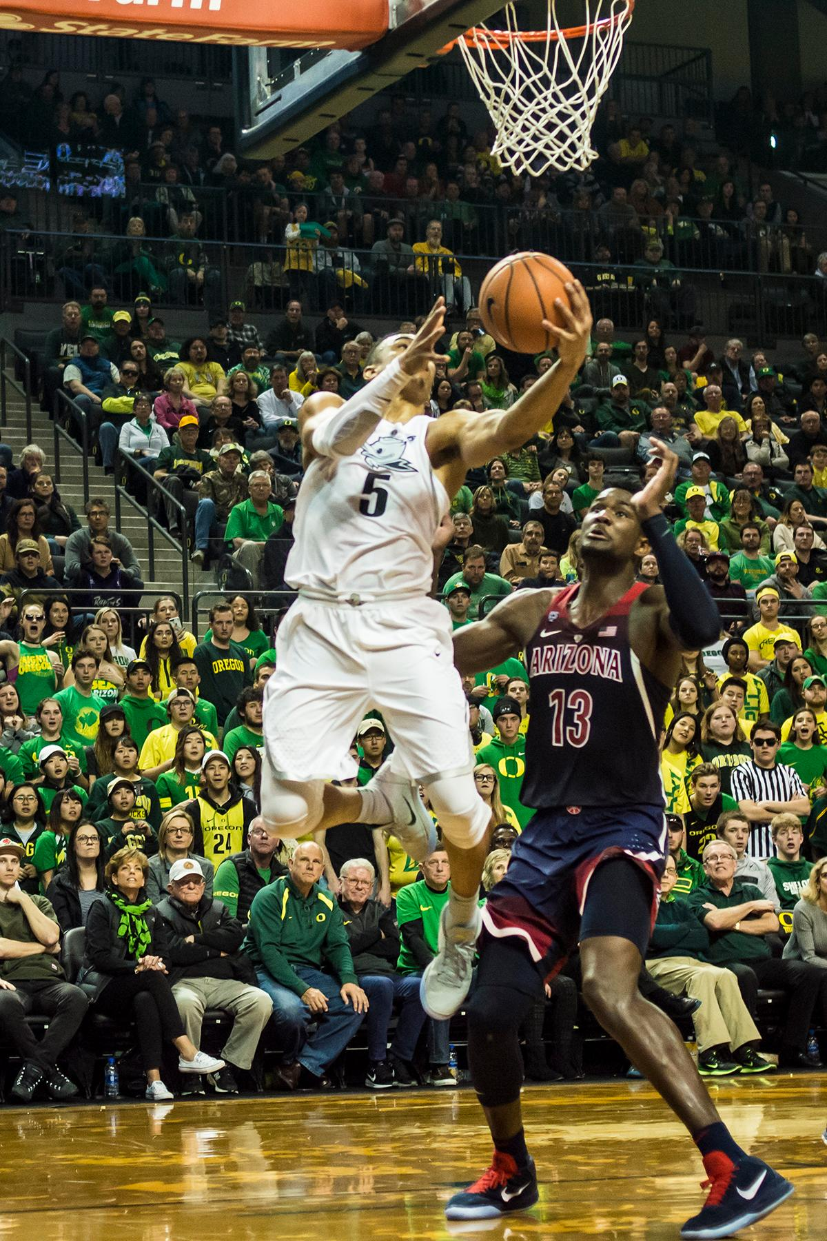 Oregon's Elijah Brown (5) goes for a layup against Arizona Wildcat's DeAndre Ayton (13) in their matchup at Matthew Knight Arena Saturday. The Ducks upset the fourteenth ranked Wildcats 98-93 in a stunning overtime win in front of a packed house of over 12,000 fans for their final home game to improve to a 19-10 (9-7 PAC-12) record on the season. Oregon will finish out regular season play on the road in Washington next week against Washington State on Thursday, then Washington on the following Saturday. (Photo by Colin Houck)