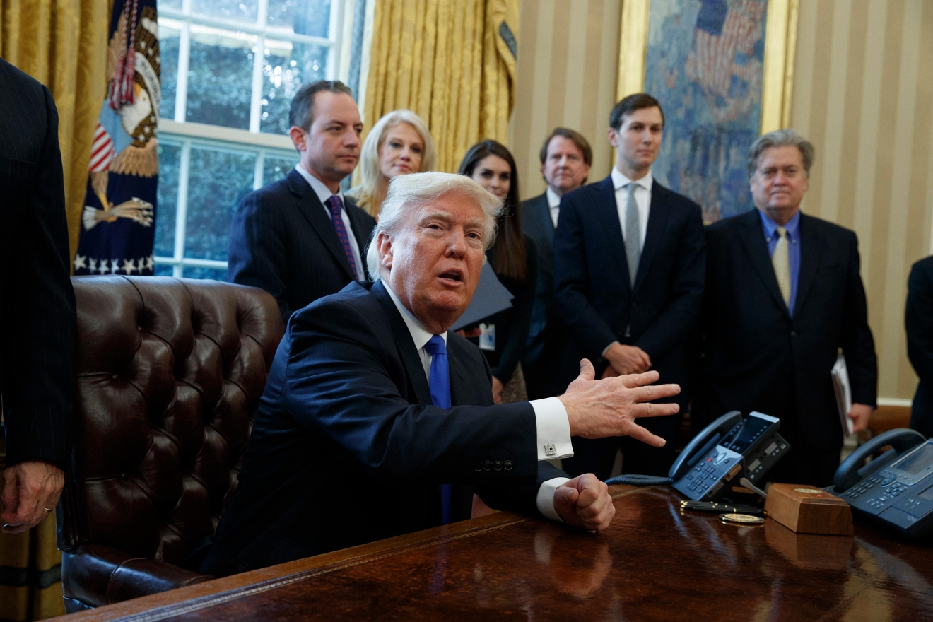 President Donald Trump talks with reporters n the Oval Office of the White House in Washington, Tuesday, Jan. 24, 2017, before signing an executive order on the Keystone XL pipeline. (AP Photo/Evan Vucci)