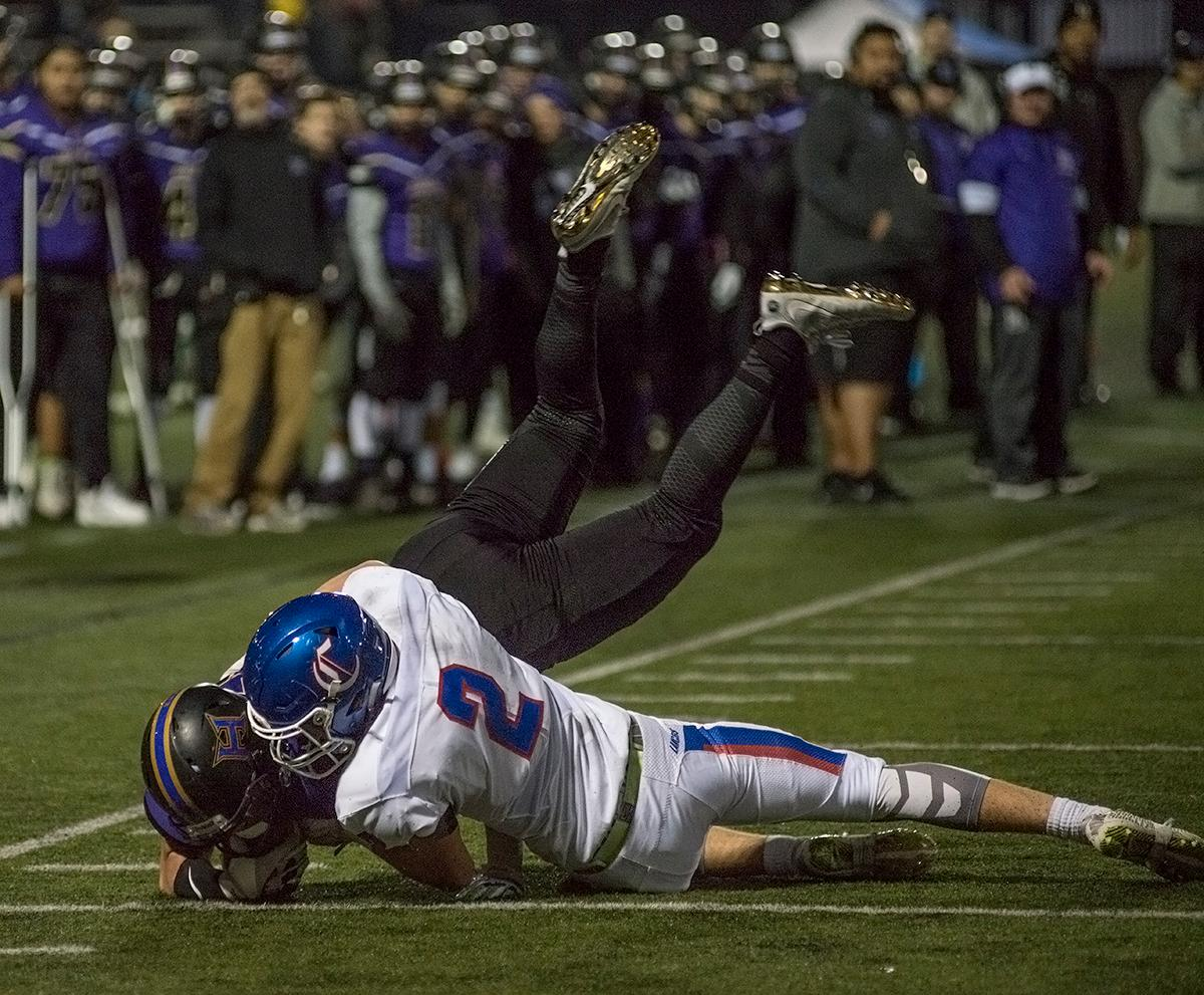 Churchill Lancers defensive back Josh Hatten (#2) tackles the Hermiston Bulldogs ball carrier right before the ball crosses the goal line.The Hermiston Bulldogs defeated the Churchill Lancers 38-35 for the 5A state title Saturday evening at Hillsboro Stadium. Photo by Abigail Winn, Oregon News Lab