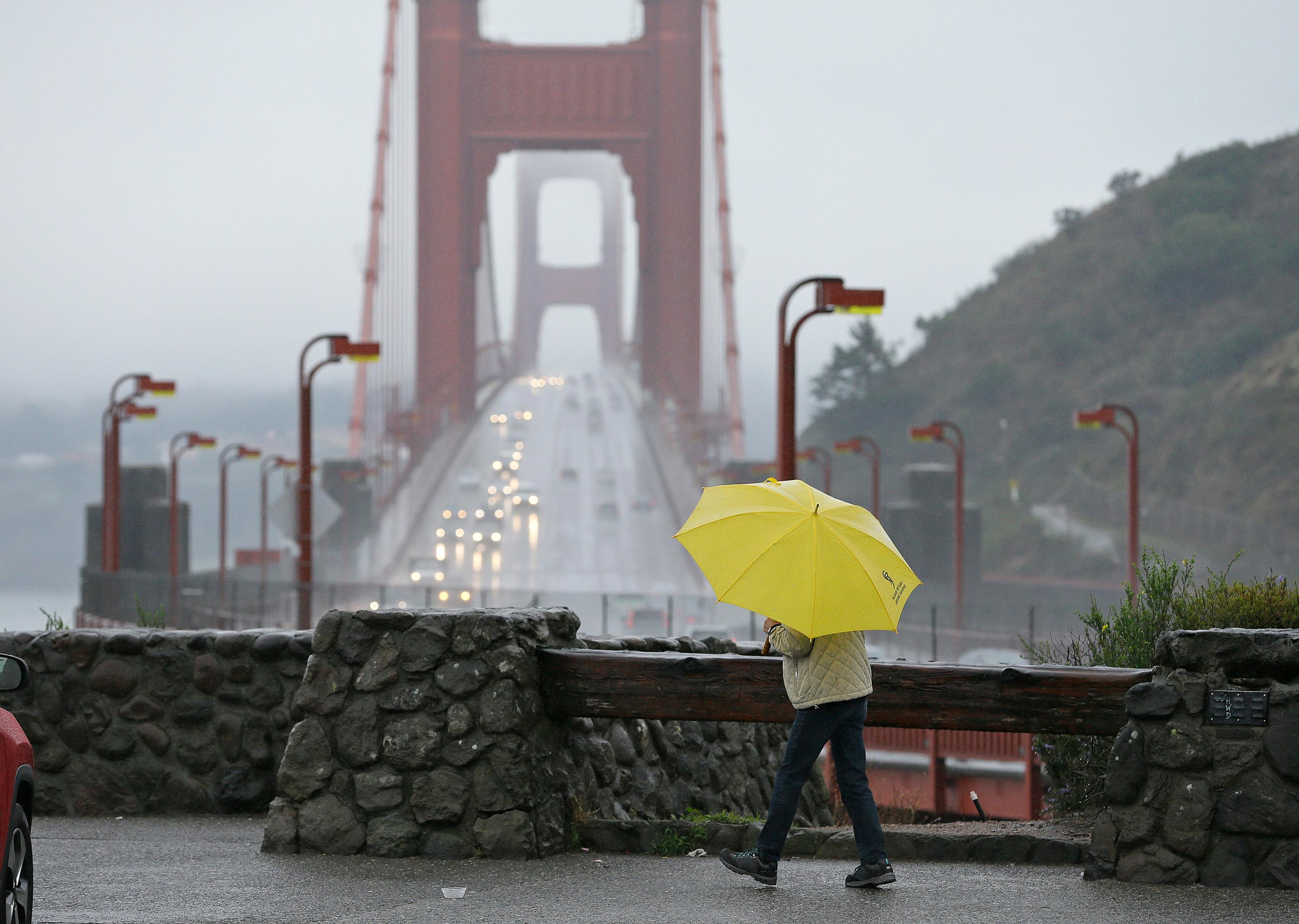 A woman walks in the rain at a vista point with the Golden Gate Bridge in the background Monday, Jan. 8, 2018, near Sausalito, Calif. Storms brought rain to California on Monday and increased the risk of mudslides in fire-ravaged communities in devastated northern wine country and authorities to order evacuations farther south for towns below hillsides burned by the state's largest-ever wildfire. (AP Photo/Eric Risberg)