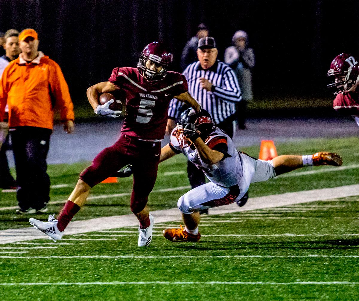 Willamette's Tanner Branson (#5) goes on a 30 yard run as Roseburg attempts to bring him down. The Roseburg Indians defeated the Willamette Wolverines 21-20 at Willamette on Friday. Photo by August Frank, Oregon News Lab