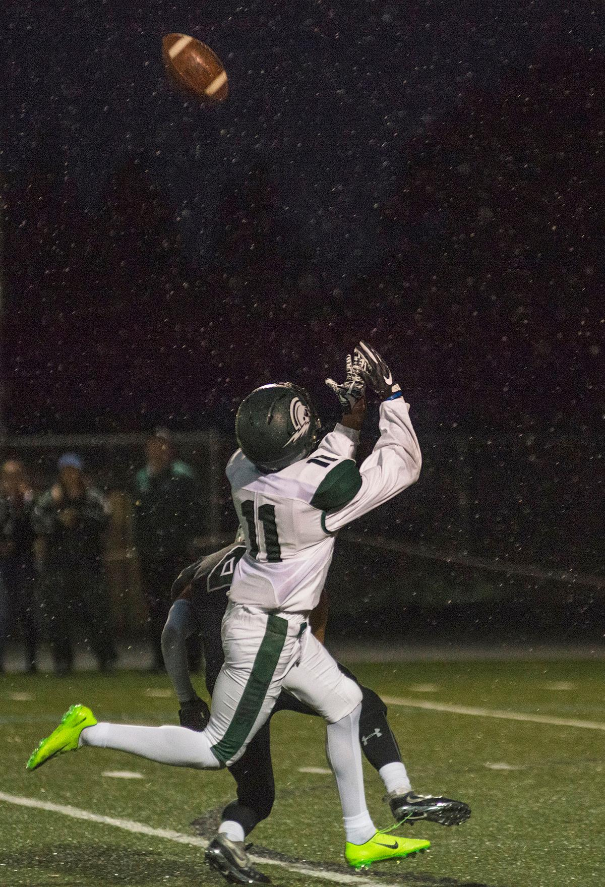 West Salem Titans wide receiver Stanley Green (#7) runs to catch the ball.  On a rainy Monday evening, Sheldon defeated West Salem 41 to 7 at their home field. The game had been postponed from Friday due to unhealthy levels of smoke in the atmosphere from nearby forest fires. Abigail Winn, Oregon News Lab