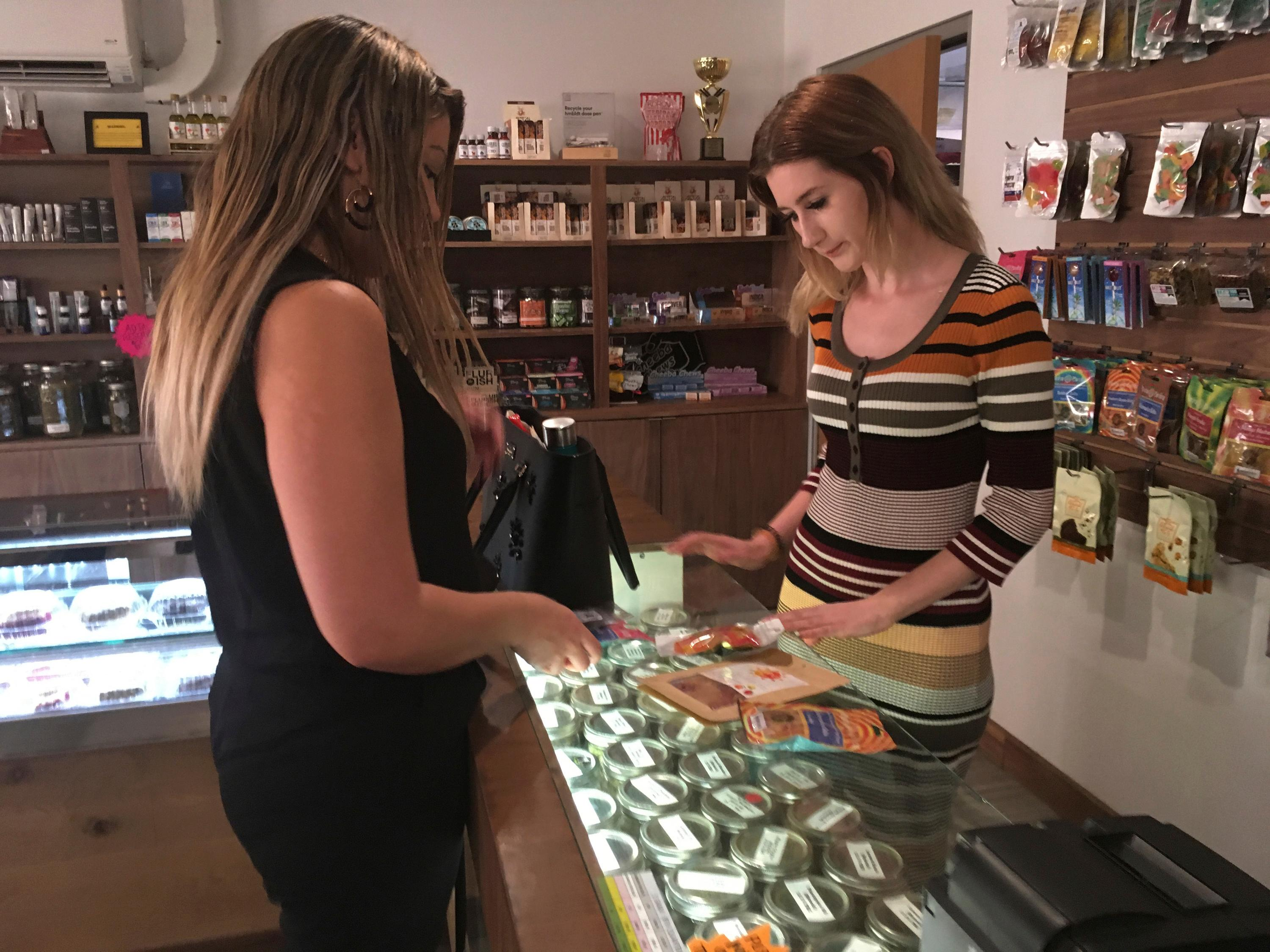 "In this Dec. 27, 2017 photo, Golden State Greens ""budtender"" Olivia Vugrin, right, waits on a customer in San Diego, Calif. Dozens of California shops have cleared a final hurdle to sell marijuana for recreational use starting Monday, Jan. 1, 2018, and regulators will work through the weekend to grant more licenses. (AP Photo/Elliot Spagat)"