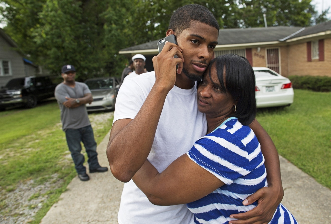 Beverly Blakes, the aunt of fallen Baton Rouge policeman Montrell Jackson, hugs Kedrick Pitts, the half-brother of slain Baton Rouge Policeman, Cpl. Jackson, after visiting Montrell's mother's house in Baton Rouge, La., Sunday, July 17, 2016. Jackson was one of the law enforcement officers who were shot and killed on Sunday morning. (AP Photo/Max Becherer)