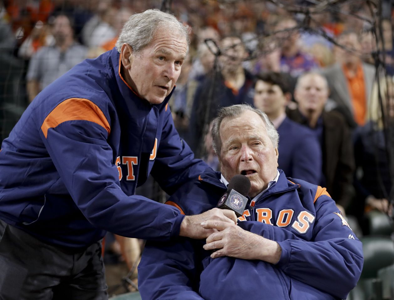 "George H.W. Bush announced ""Let's play ball"" to the crowd as his son stood behind him smiling."