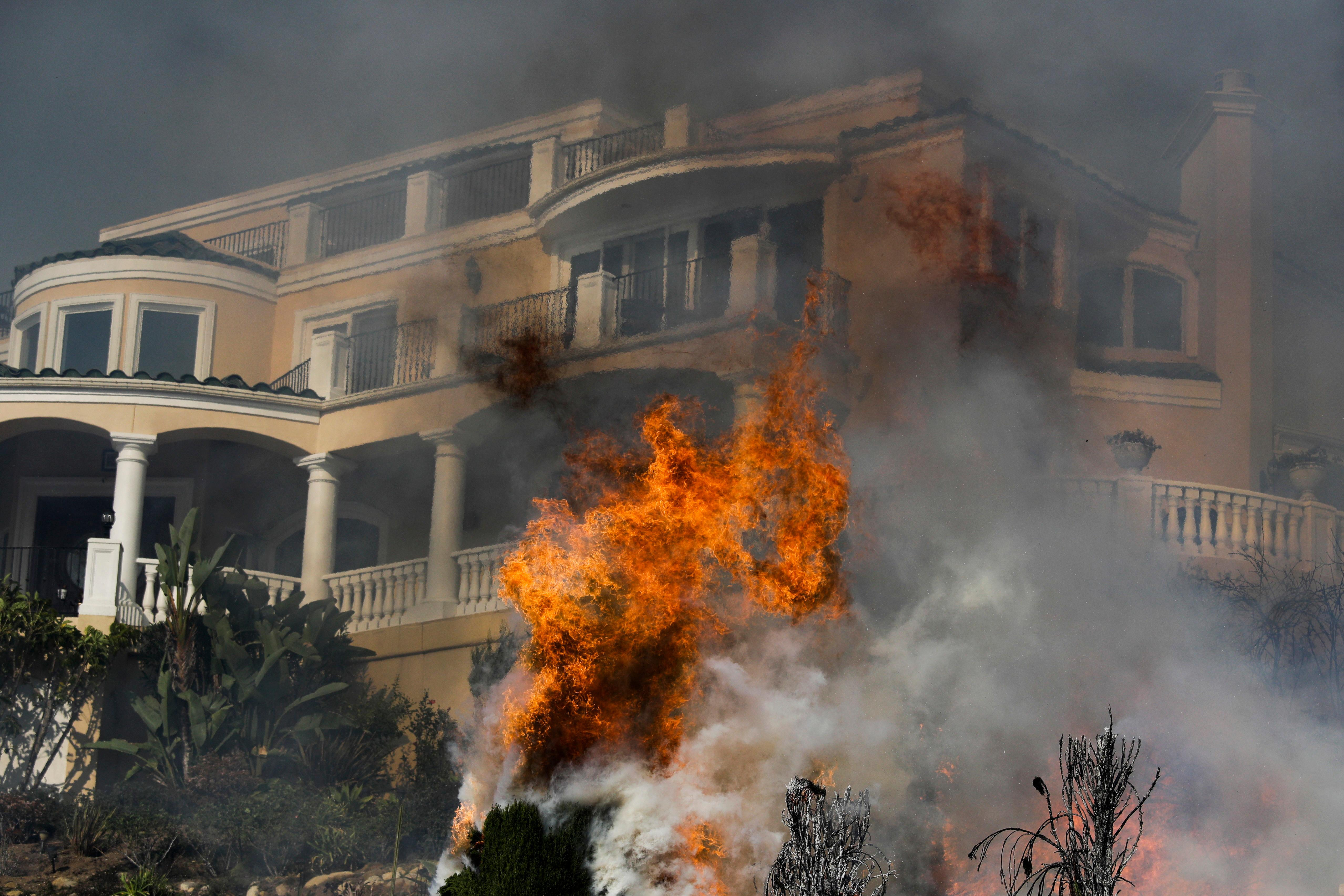 Flames rise near a home as a wildfire burns in Ventura, Calif., on Tuesday, Dec. 5, 2017. Ferocious winds in Southern California have whipped up explosive wildfires, burning a psychiatric hospital and scores of other structures. (AP Photo/Jae Hong)