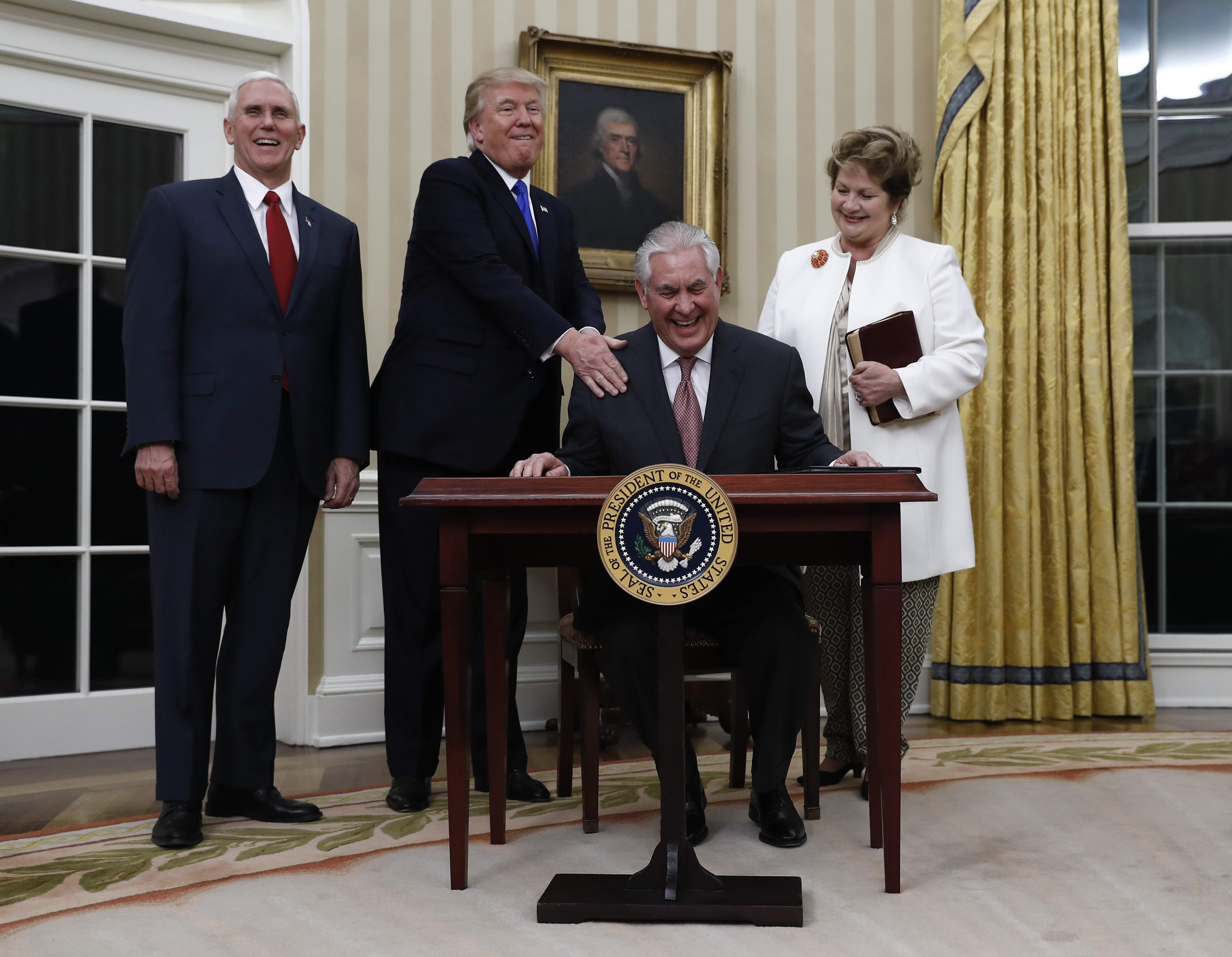 DAY 13 - In this Feb. 1, 2017, file photo, Secretary of State Rex Tillerson, joined by President Donald Trump, Vice President Mike Pence and his wife Renda St. Clair, laughs after signing the Appointment Affidavit after being sworn in as Secretary of State in the Oval Office of the White House in Washington. (AP Photo/Carolyn Kaster, File)