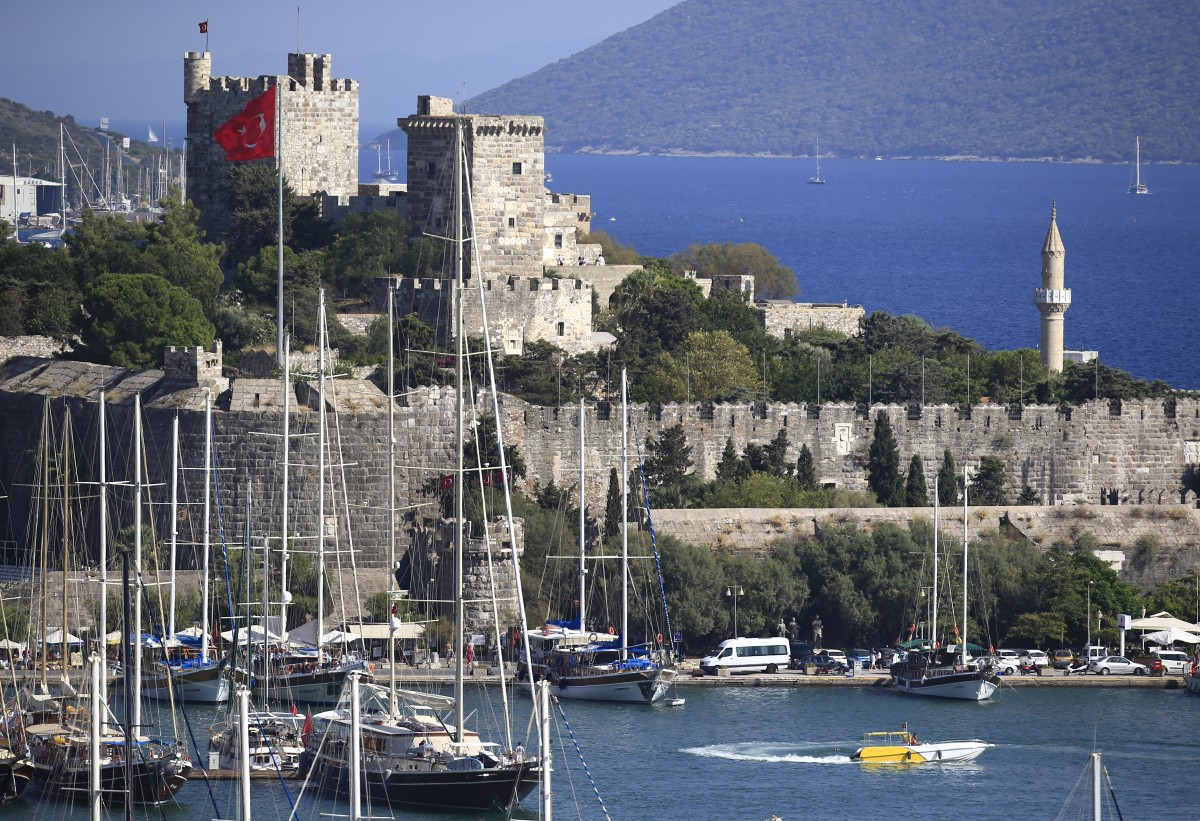 A view of the 15th century castle in the town of Bodrum, Turkey, Sunday, Aug. 16, 2015. The city of Bodrum, a magnet for wealthy tourists, is these days drawing plenty of other visitorsó migrants fleeing conflicts in the Middle East and Africa and seeking a better life in Europe. At its closest point, the Greek island of Kos is only 4 kilometers (2.5 miles) from Turkey and migrants, mostly from Syria, but also from Afghanistan, Iran and African nations often try to cross in groups upward of eight people in small inflatable plastic boats meant for a maximum of four, powered by tiny electric outboard motors and plastic paddles. (AP Photo/Lefteris Pitarakis)