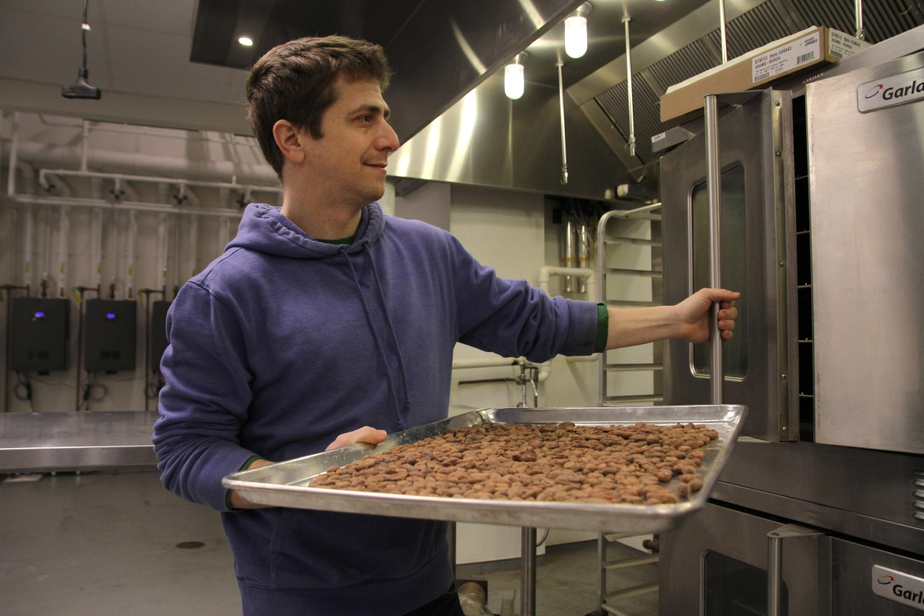 Adam places the beans inside the industrial convection oven. (Image: Amanda Andrade-Rhoades/ DC Refined)