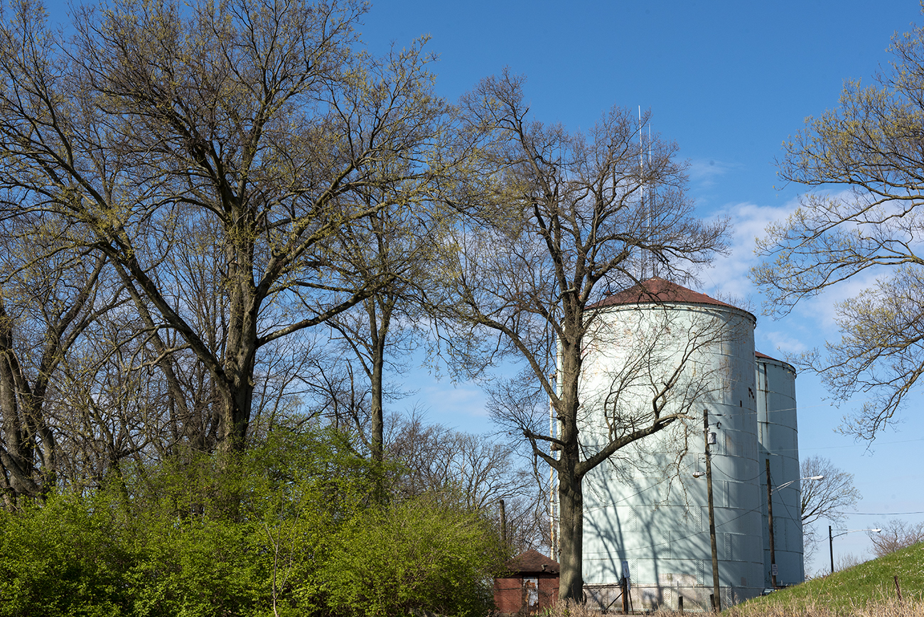 "The Norwood water towers (2529 Moundview Drive) / Sitting just beside the Norwood Mound, the Norwood water tower was listed as ""new"" in newspapers from 1894. At one time, one of the towers that exist today had a spiral staircase that wrapped around the exterior of the drum and an observation deck at the top where people could enjoy the view. Because it sits at the highest point of Norwood (over 800 feet above sea level), the tower provided a sweeping view of the neighborhood. At some point during its lifespan, the conical roof and exterior staircase were removed. Today, it no longer offers an observation deck and it sits in Norwood's Watertower Park behind several residences. / SOURCE: en-us.topographic-map.com / Image: Joe Simon // Published: 4.22.20"