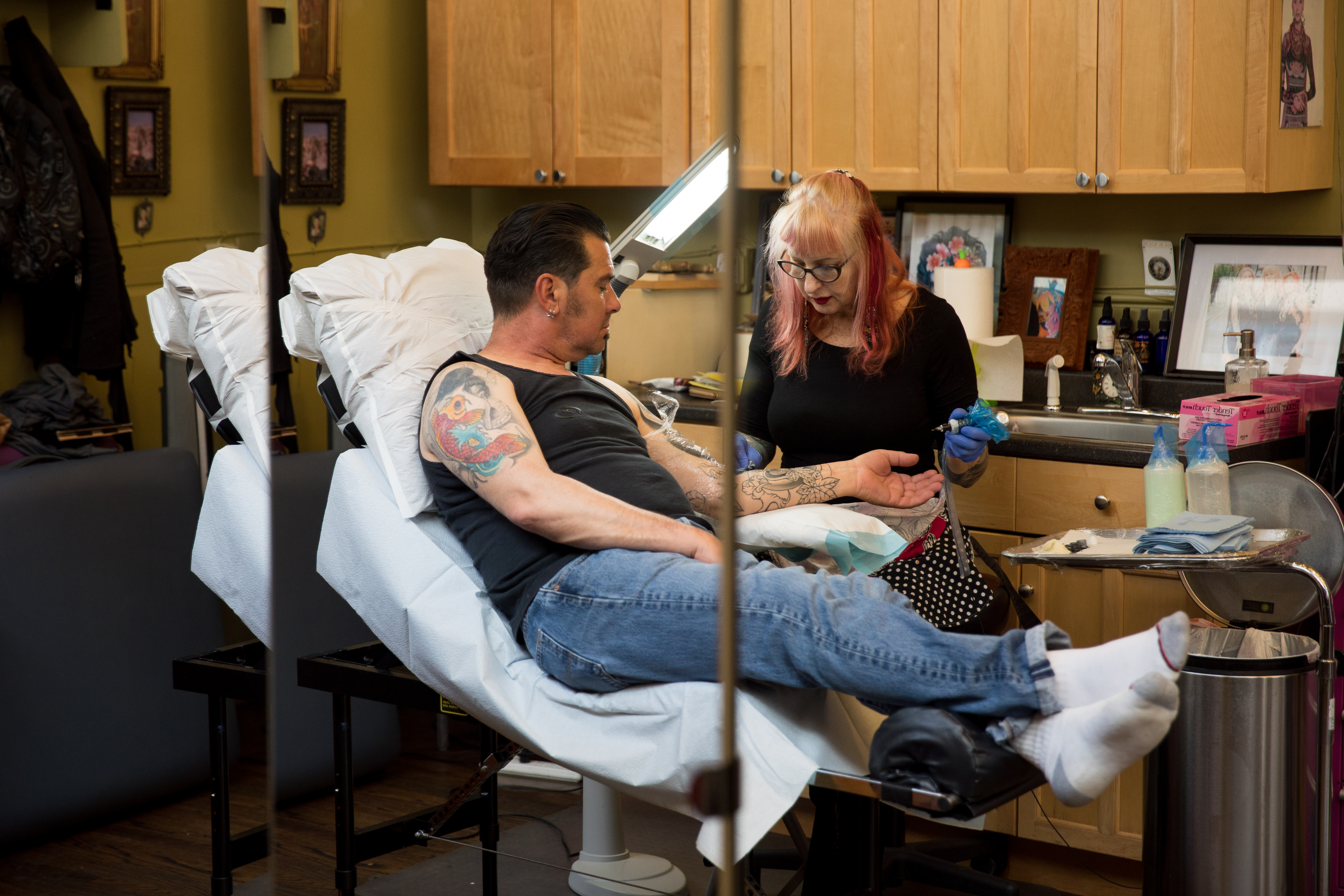 "After 46 years as a working artist, Vyvyn ""Madame"" Lazonga sees creating a tattoo as a collaboration between herself and the client. ""It' doesn't do anyone any good if the tattoo artist hates what they're doing,"" she explains. (Image: Riley Bunch / Seattle Refined)"