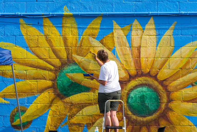 Artist Julie Harwood painted sunflowers on the side of a nearby building to tie Madhatter Park's sunflower wall in with its surroundings. / Image: Phil Armstrong, Cincinnati Refined // Published: 8.7.18