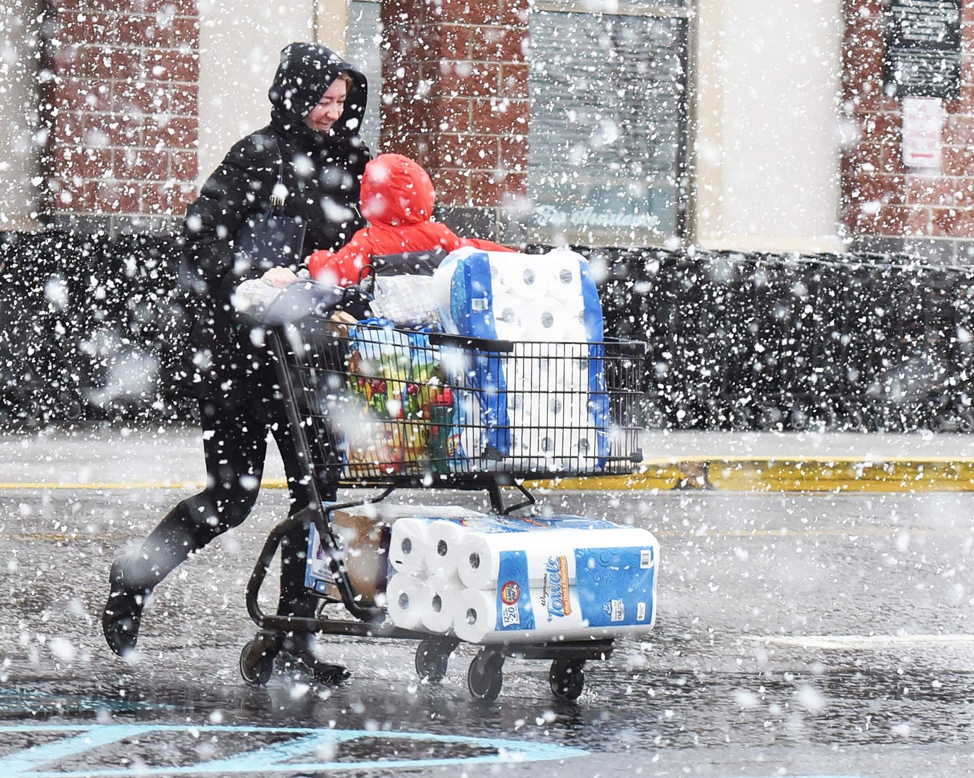 A customer hurries to her car after grocery shopping at Wegmans in Mount Laurel, on Wednesday, March 7, 2018, as the wintry mix was changing into snow. [NANCY ROKOS / STAFF PHOTOJOURNALIST]