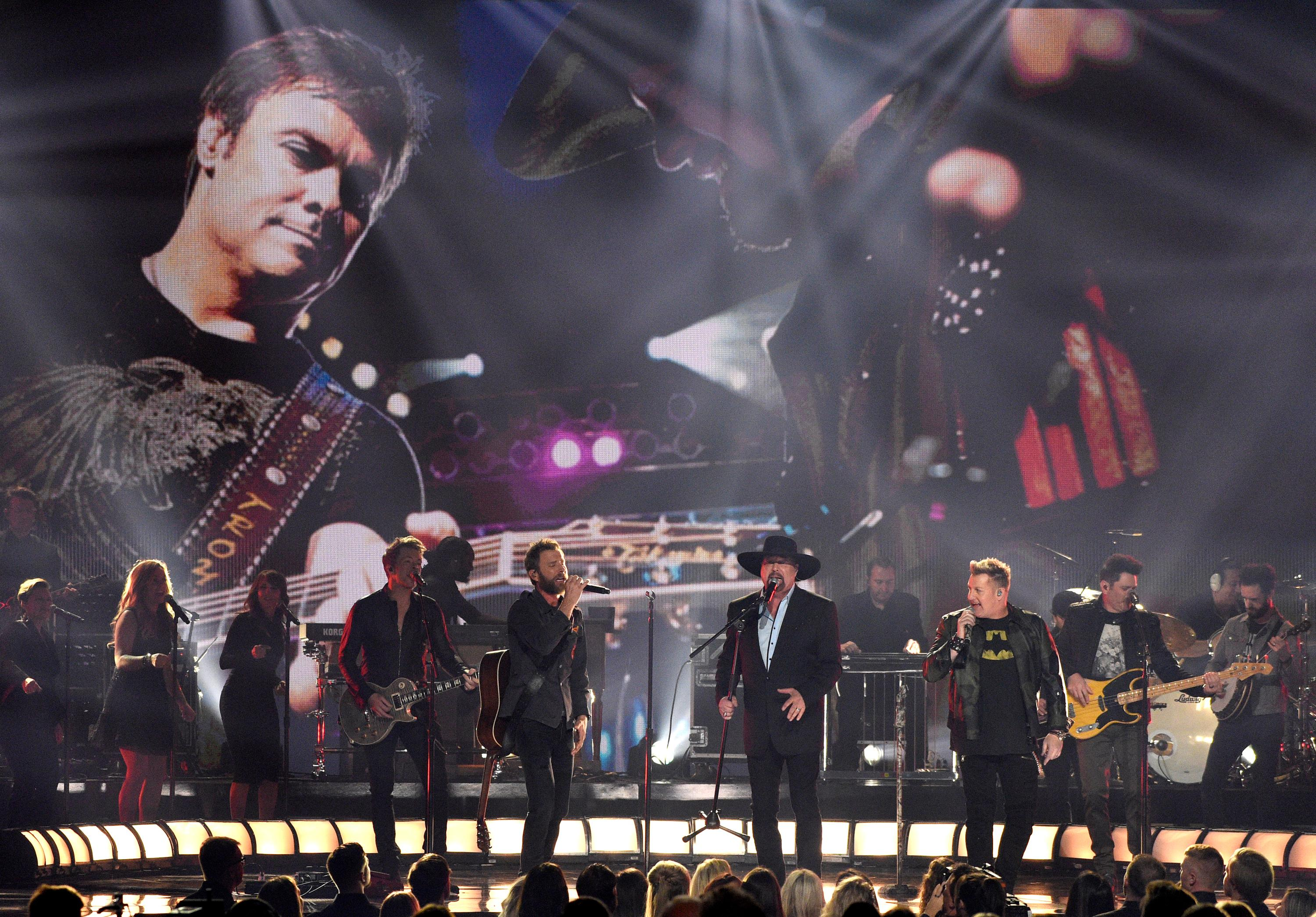 "Joe Don Rooney,from left, Dierks Bentley,Eddie Montgomery,Gary LeVox, and Jay DeMarcus perform ""My Town""during a tribute to Troy Gentry at the 51st annual CMA Awards at the Bridgestone Arena on Wednesday, Nov. 8, 2017, in Nashville, Tenn. (Photo by Chris Pizzello/Invision/AP)"