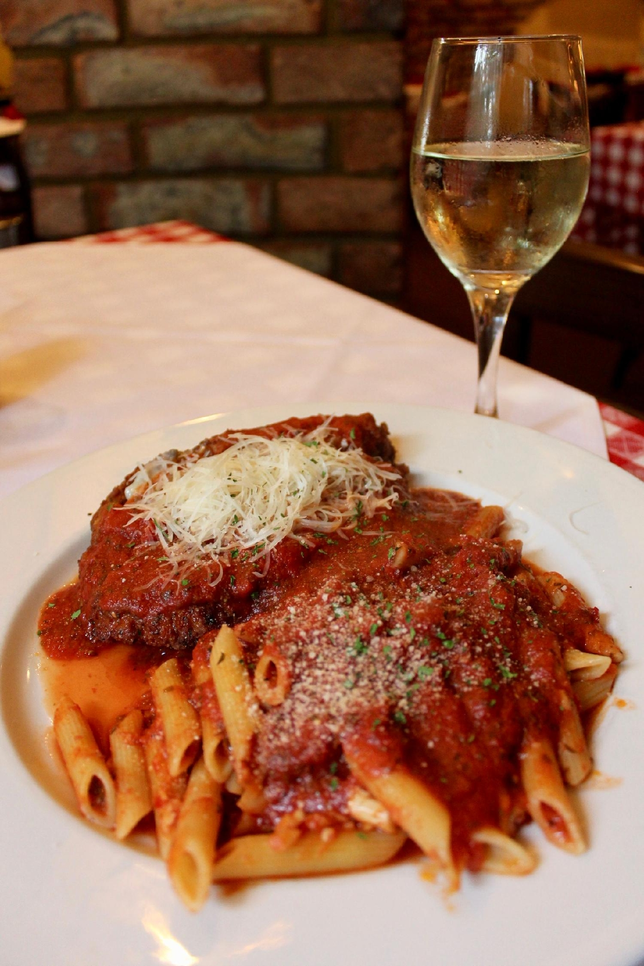 Pollo Parmesan: chicken milanese, provalone cheese, marinara sauce, and rigatoni (with Ferrari's House Pinot Grigio) / Image: Rose Brewington