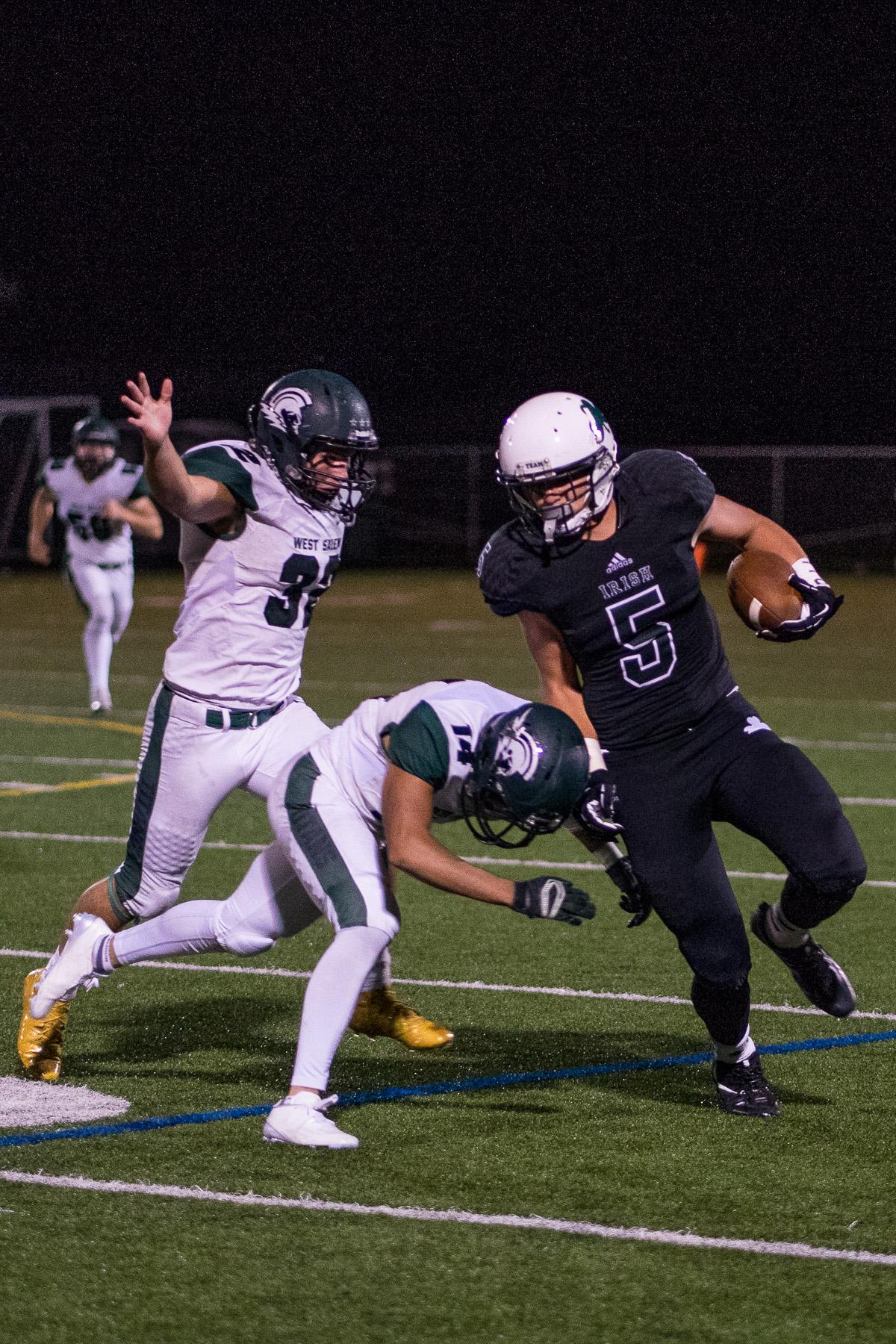 Sheldon Irish wide receiver Patrick Herbert (#5) is pressured by West Salem's defense. On a rainy Monday evening, Sheldon defeated West Salem at home 41 – 7. The game had been postponed until Monday, September 18, due to unhealthy levels of smoke in the air caused by nearby forest fires. Photo by Kit MacAvoy, Oregon News Lab