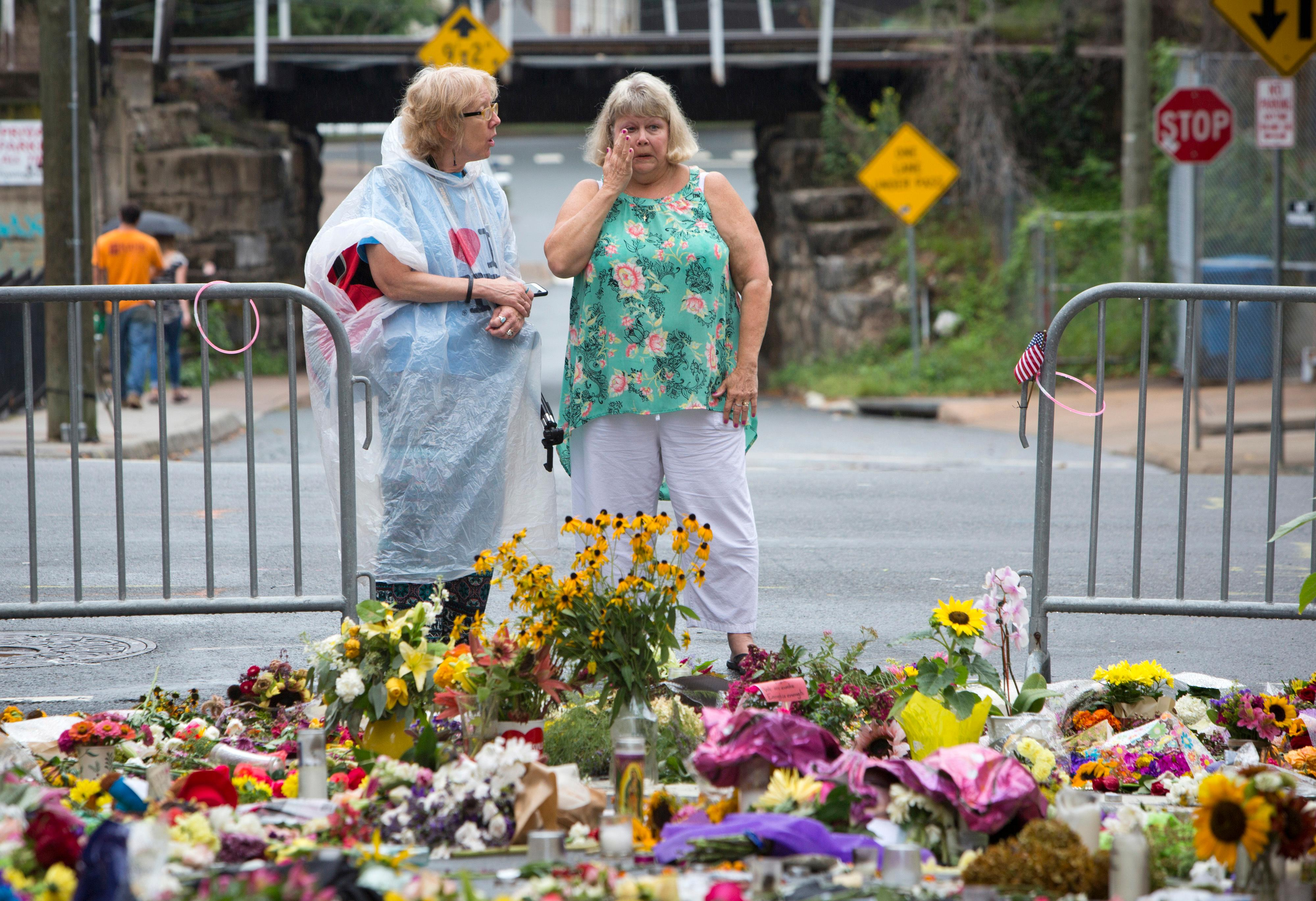 Women visit a memorial at 4th and Water Streets, Tuesday, Aug. 15 2017,  in Charlottesville, Va., where Heather Heyer was killed when a car rammed into a group of counterprotesters last weekend. Alex Fields Jr., is charged with second-degree murder and other counts after authorities say he rammed his car into a crowd of counterprotesters Saturday, where a white supremacist rally took place.  (AP Photo/Julia Rendleman)