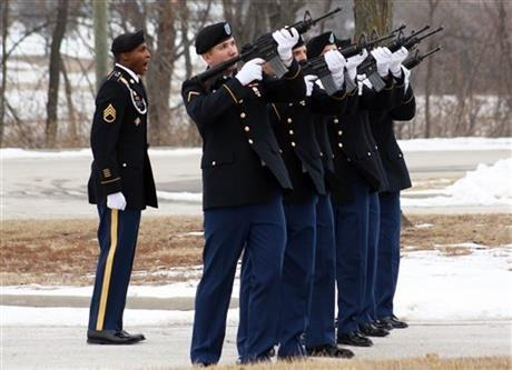 Staff Sgt. Michael Smith, left, gives the command to soldiers to fire a round in a 21-volley salute Thursday, Jan. 9, 2014, during a memorial service at Fort Riley, Kan. Soldiers and families paid their respects to five soldiers who were killed.