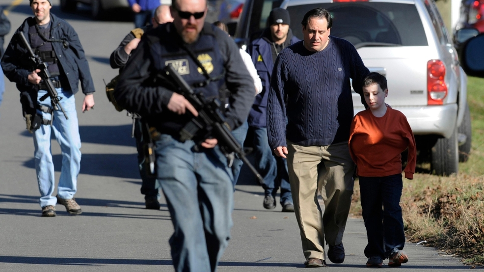 14, 2012 file photo, parents leave a staging area after being reunited with  their children following a shooting at the Sandy Hook Elementary School in  ...