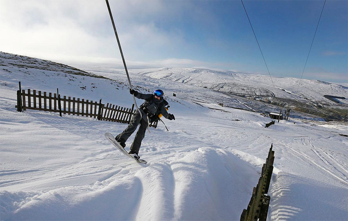 A snowboarder takes a lift at Yad Moss ski slope near Alston in the North Pennines, England, on the resort's first day of the skiing and boarding season, Wednesday Nov. 23, 2016. (Owen Humphreys / PA via AP)
