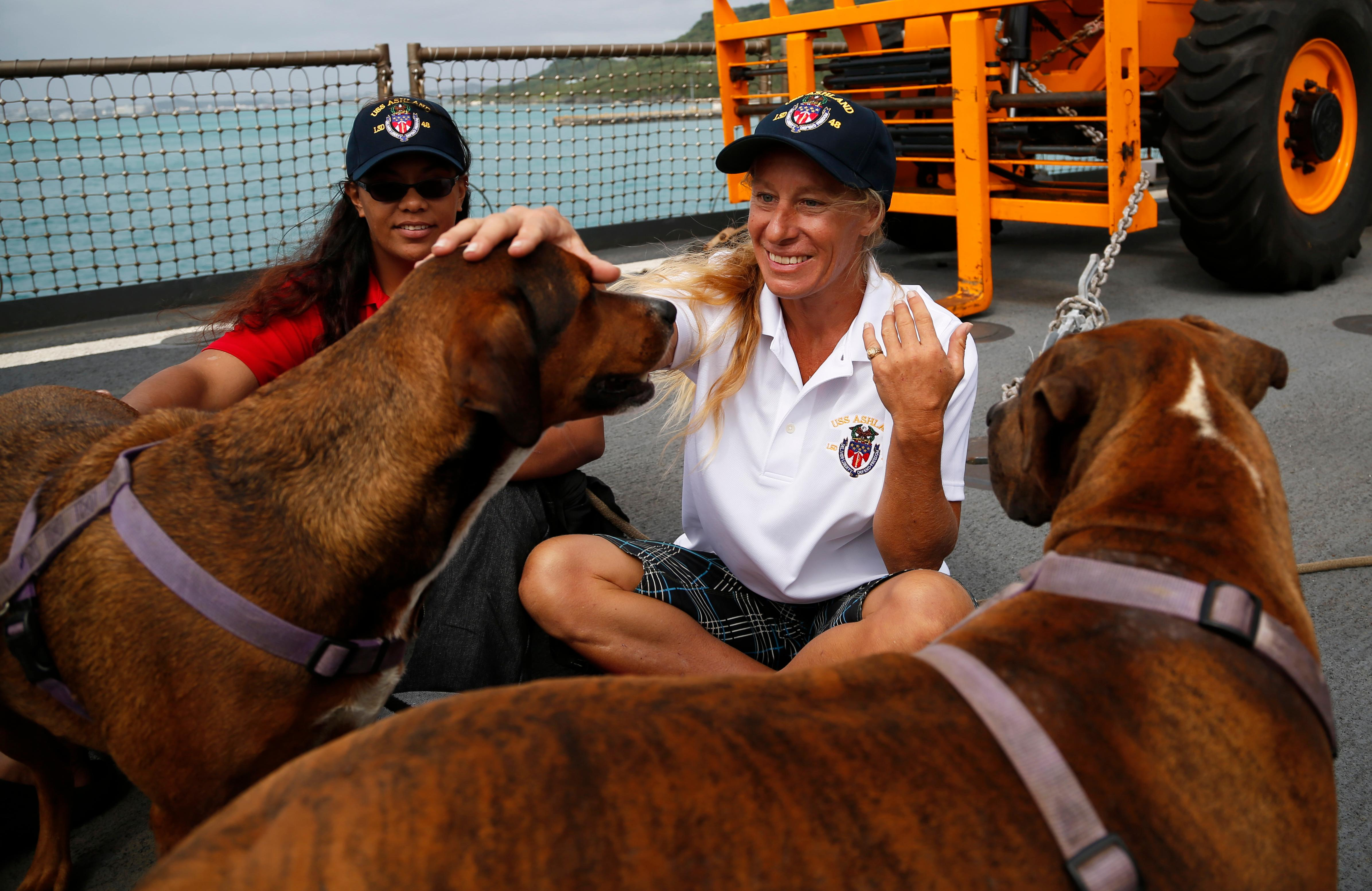 Jennifer Appel, right, and Tasha Fuiava sit with their dogs on the deck of the USS Ashland Monday, Oct. 30, 2017, at White Beach Naval Facility in Okinawa, Japan. (AP Photo/Koji Ueda)<p></p>