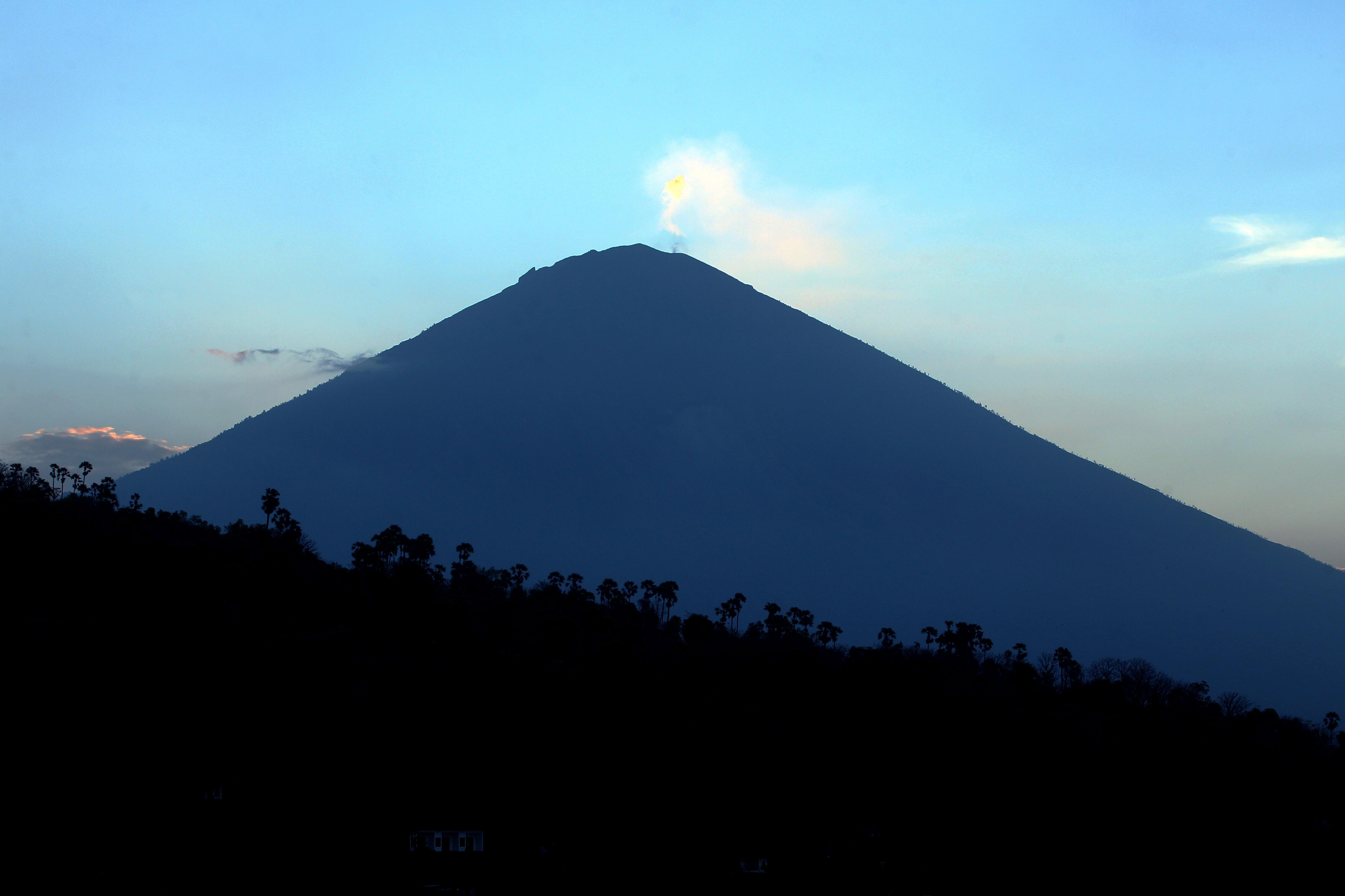 Mount Agung volcano is seen at sunset in Karangasem, Bali, Indonesia, Thursday, Sept. 28, 2017. More than 120,000 people have fled the region around the Mount Agung volcano on the Indonesian tourist island of Bali, fearing it will soon erupt, an official said Thursday. (AP Photo/Firdia Lisnawati)