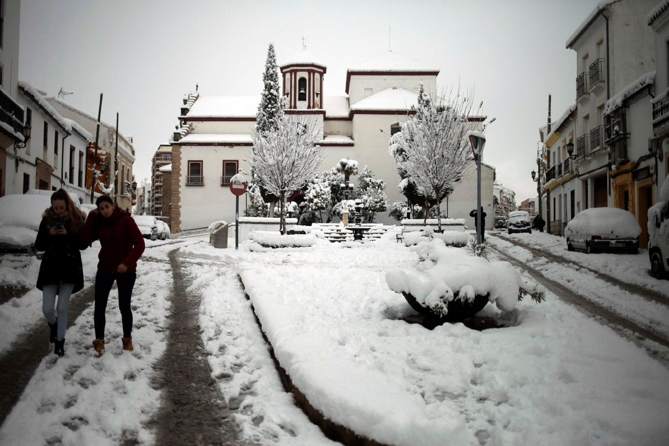 People walk carefully through a street after snowfall in the city of Ronda, southern Spain, Thursday, Jan. 19, 2017.  (AP Photo/Javier Gonzalez)