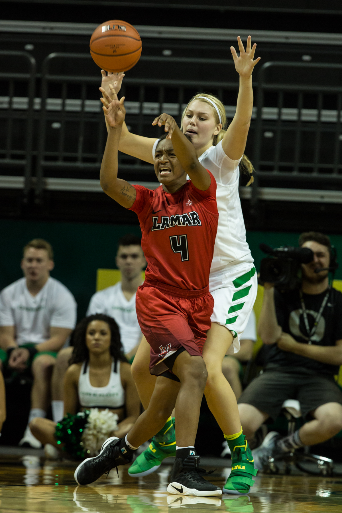 Lamar Cardinals point guard Briana Laidler (#4) passes the ball under intense pressure from an Oregon defender. The Oregon Ducks Women's basketball team won their season opener against the Lamar Cardinals 84-67.  Photo by Austin Hicks, Oregon News Lab