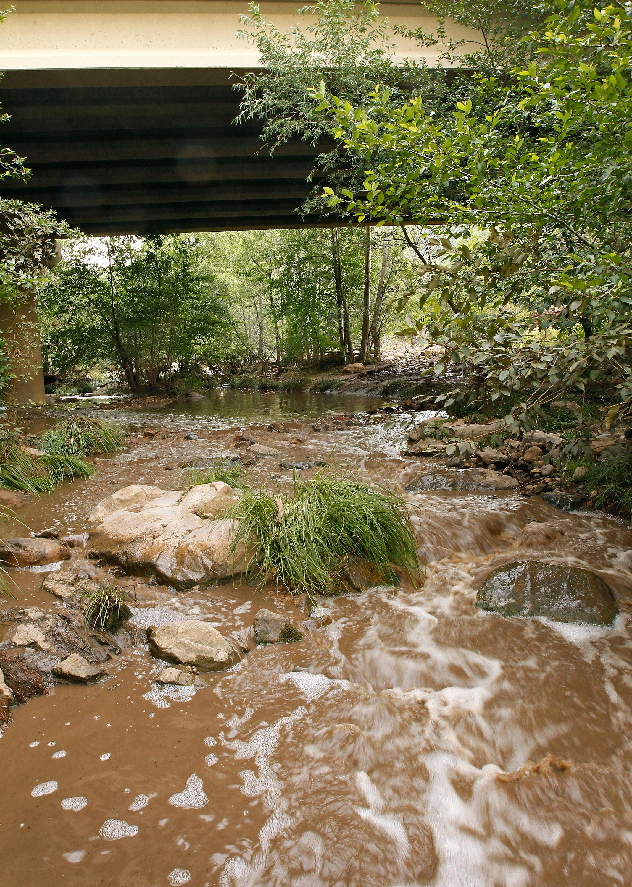 Muddy floodwaters of the East Verde River flow under a bridge where at least one victim of a flash flood was found during a search and rescue operation by the Gila County Sheriff's Office on Sunday, July 16, 2017, in Payson, Ariz. Search and rescue crews, including 40 people on foot and others in a helicopter, have recovered bodies of children and adults, some as far as two miles down the river after Saturday's flash flooding poured over a popular swimming area inside the Tonto National Forest in central Arizona. (AP Photo/Ralph Freso)
