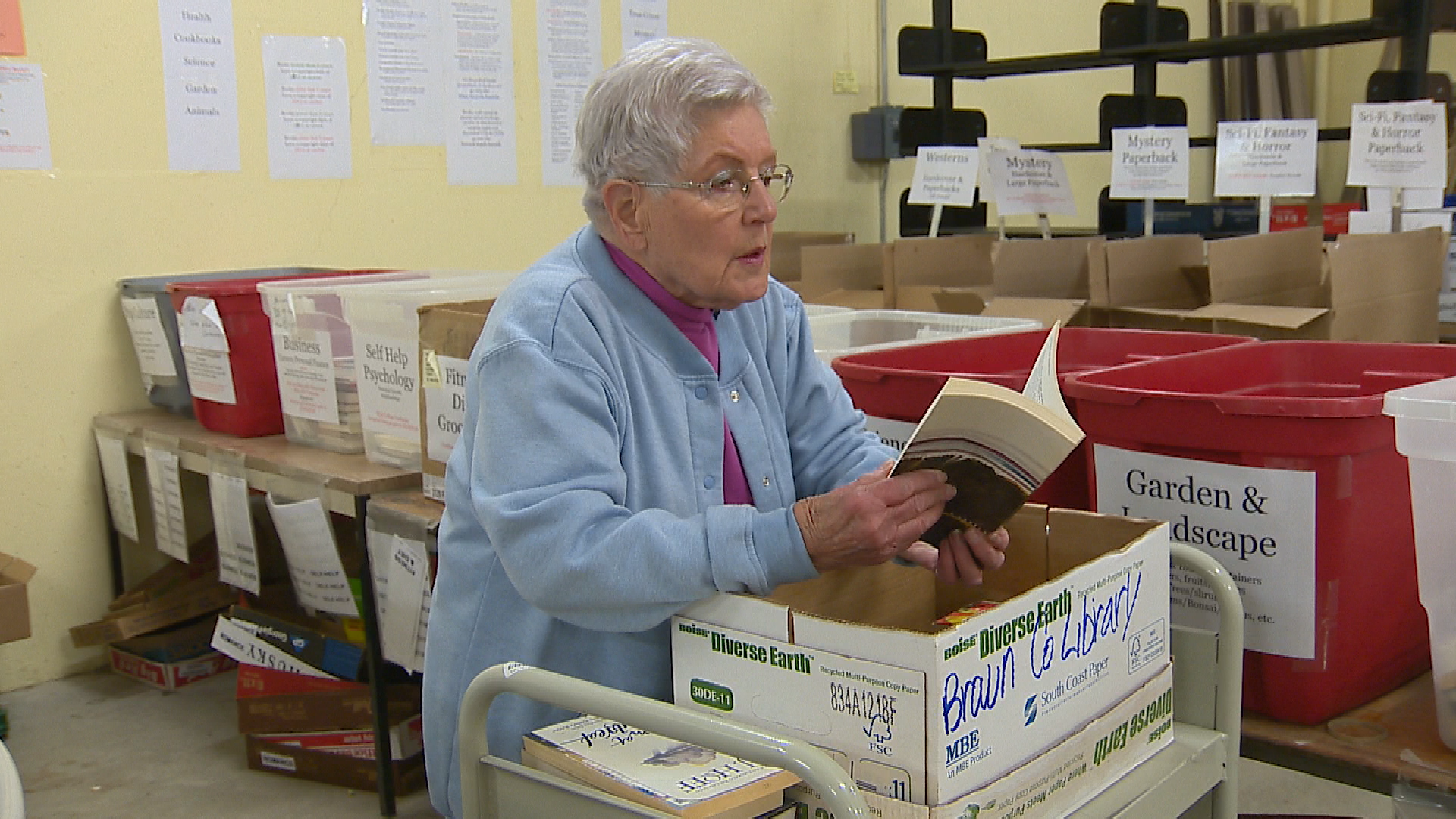 Anita Powers sifting through books to sort ahead of the twice-yearly book sale. (Courtesy WLUK)<p></p>