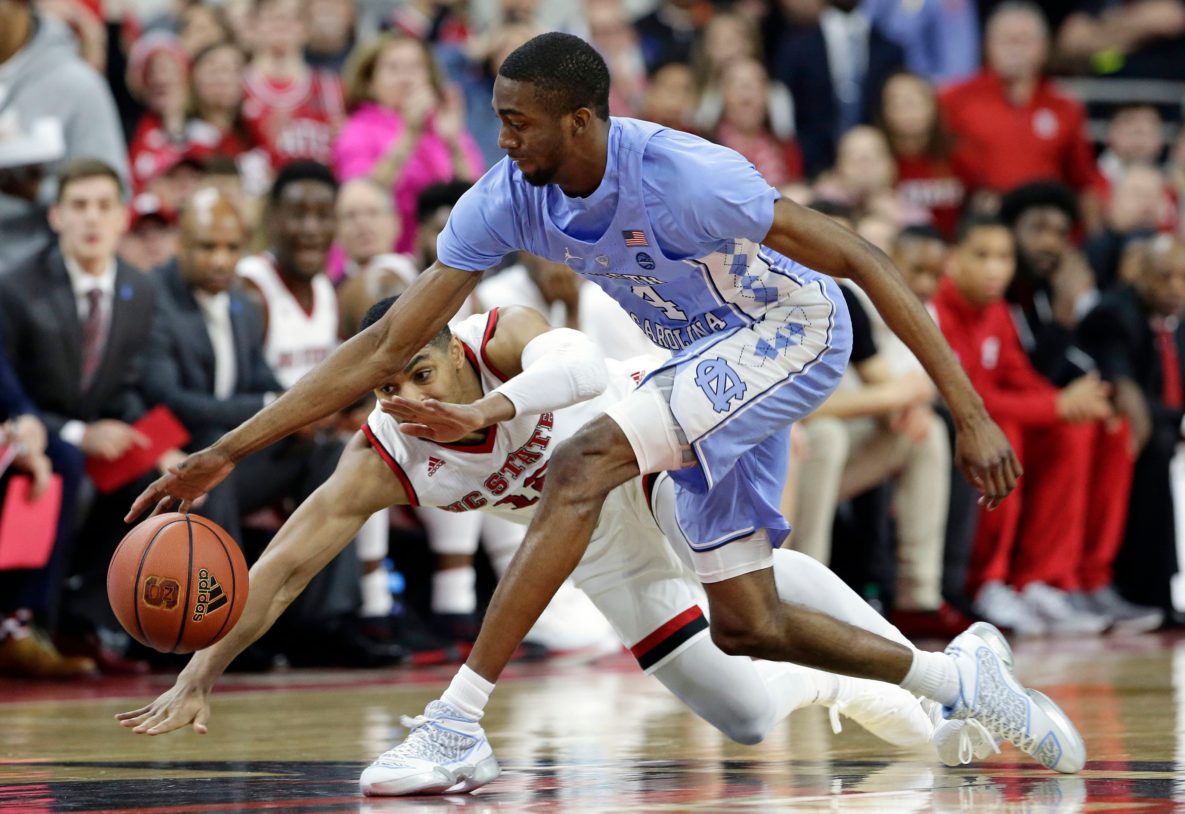 North Carolina's Brandon Robinson (4) and North Carolina State's Allerik Freeman chase a loose ball during the first half of an NCAA college basketball game in Raleigh, N.C., Saturday, Feb. 10, 2018. (AP Photo/Gerry Broome)