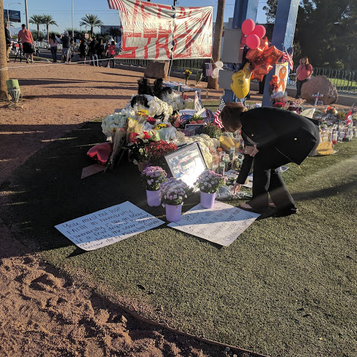 A woman leaves flowers as she begins paying her respects to the 58 shooting victims at the Welcome to Las Vegas sign on Friday, Oct. 7, 2017. (Marvin Clemons | KSNV)<p></p>