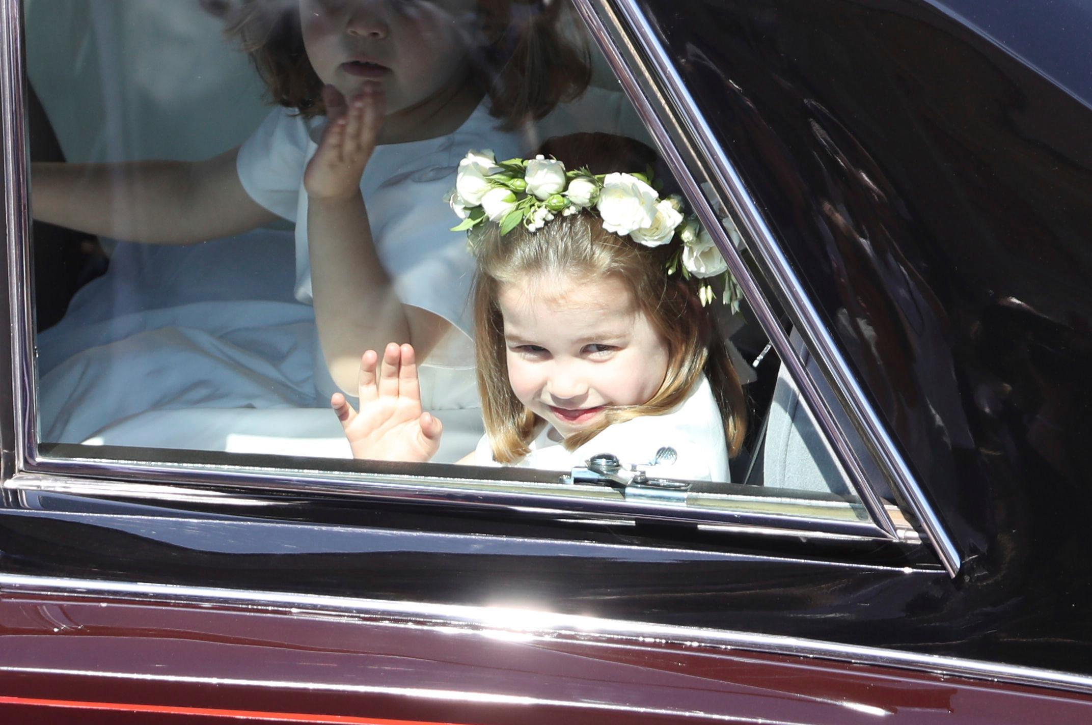 Princess Charlotte waves as she rides in a car to the wedding ceremony of Prince Harry and Meghan Markle at St. George's Chapel in Windsor Castle in Windsor, near London, England, Saturday, May 19, 2018. (Andrew Milligan/pool photo via AP)
