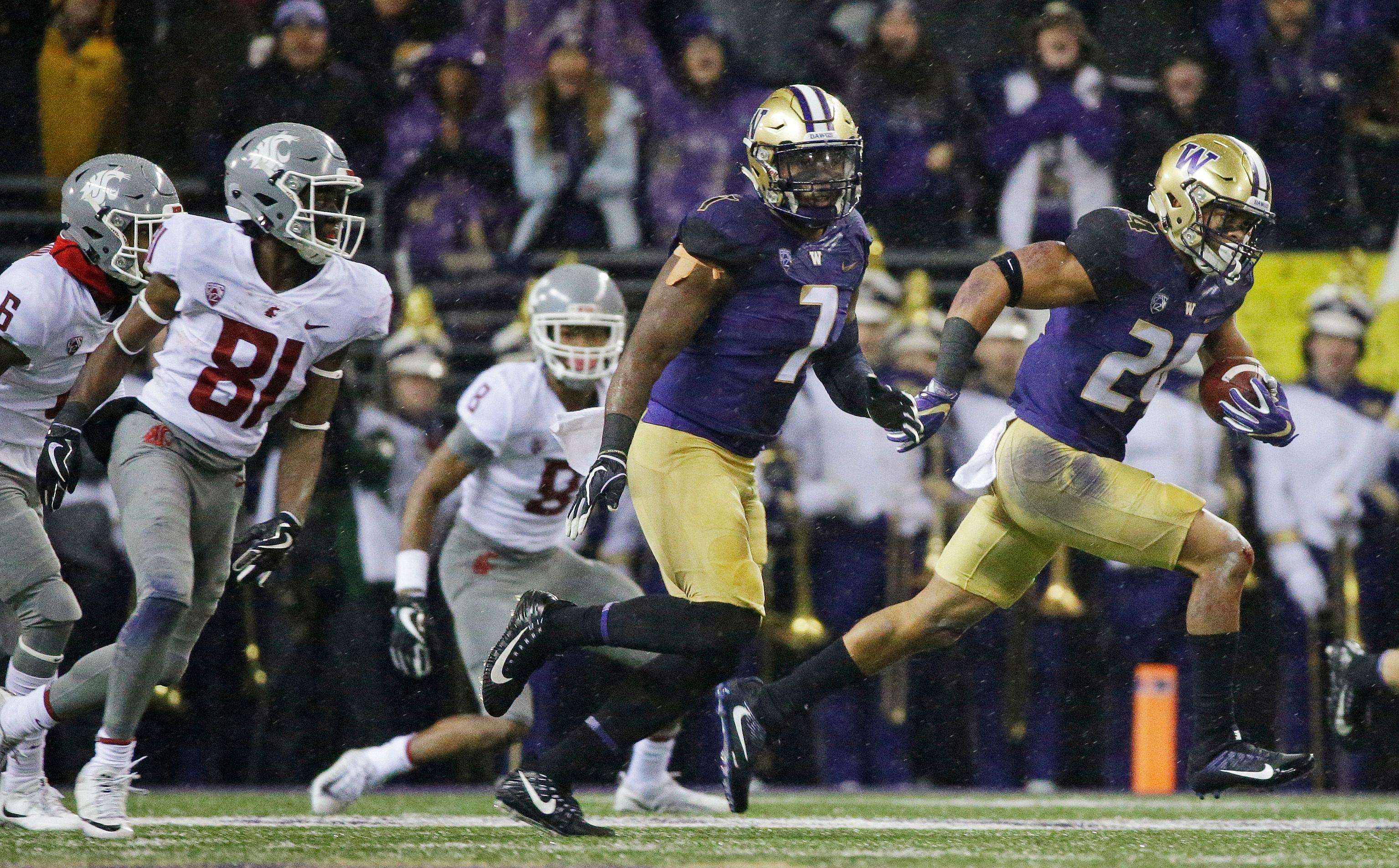 Washington defensive back Ezekiel Turner, right, runs with the ball after he intercepted a Washington State pass during the first half of an NCAA college football game, Saturday, Nov. 25, 2017, in Seattle. (AP Photo/Ted S. Warren)