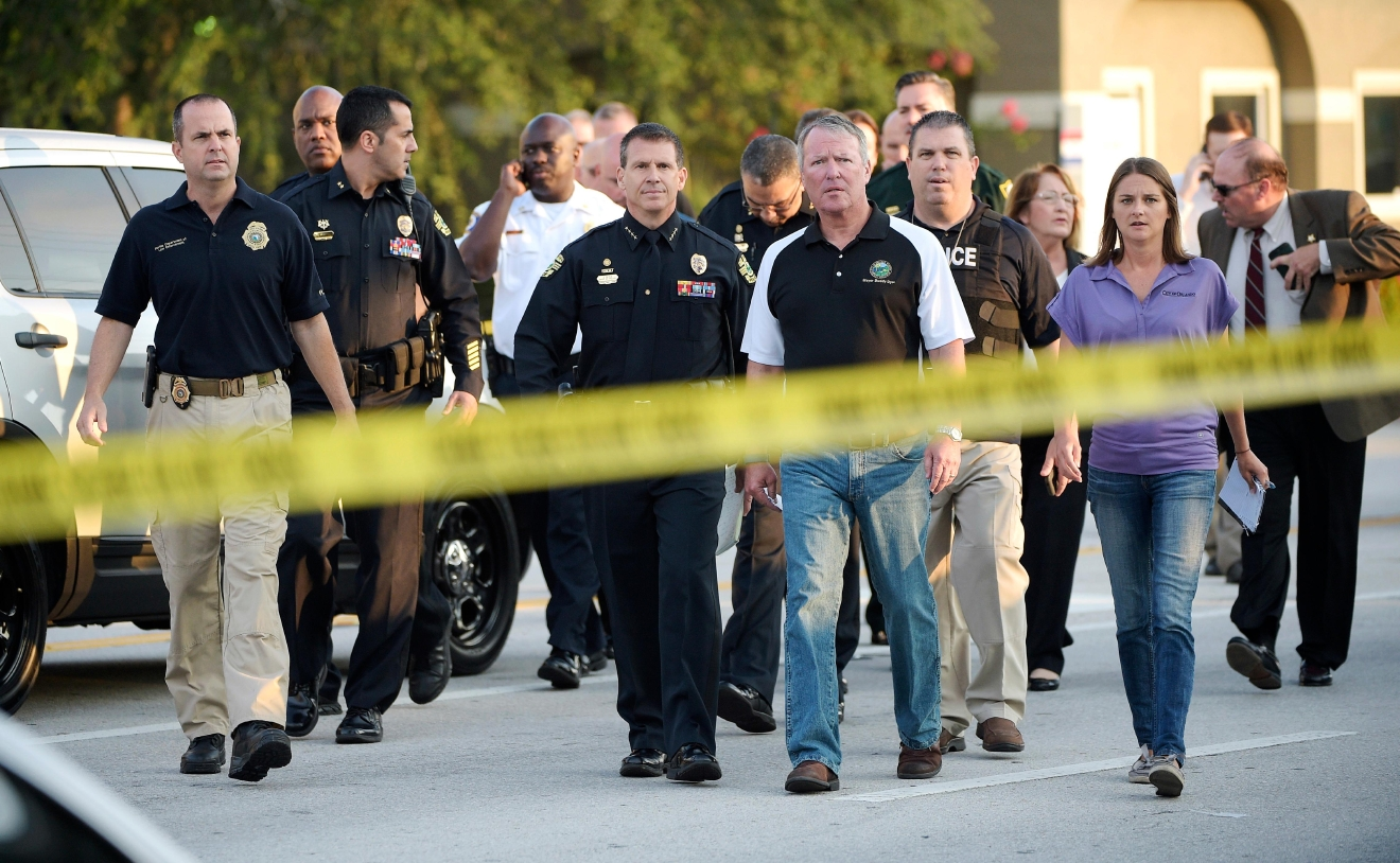 Orlando Mayor Buddy Dyer, center right, and Orlando Police Chief John Mina, center left, arrive to a news conference after a fatal shooting at Pulse Orlando nightclub in Orlando, Fla., Sunday, June 12, 2016. (AP Photo/Phelan M. Ebenhack)