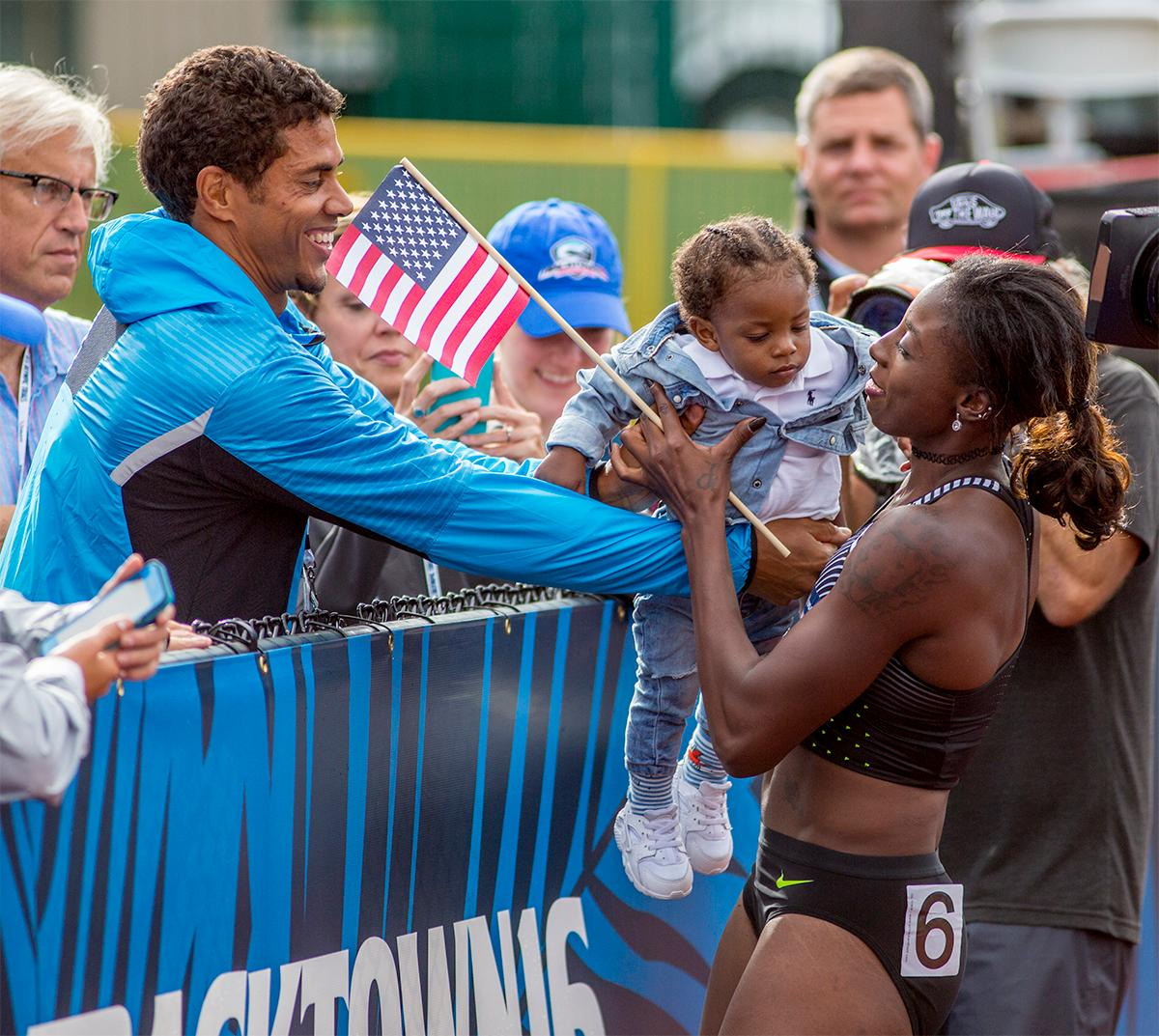 Nike's Nia Ali is handed her baby Titus for her victory lap after taking third in the 100 meter hurdles with at time of 12.55. Photo by August Frank, Oregon News Lab