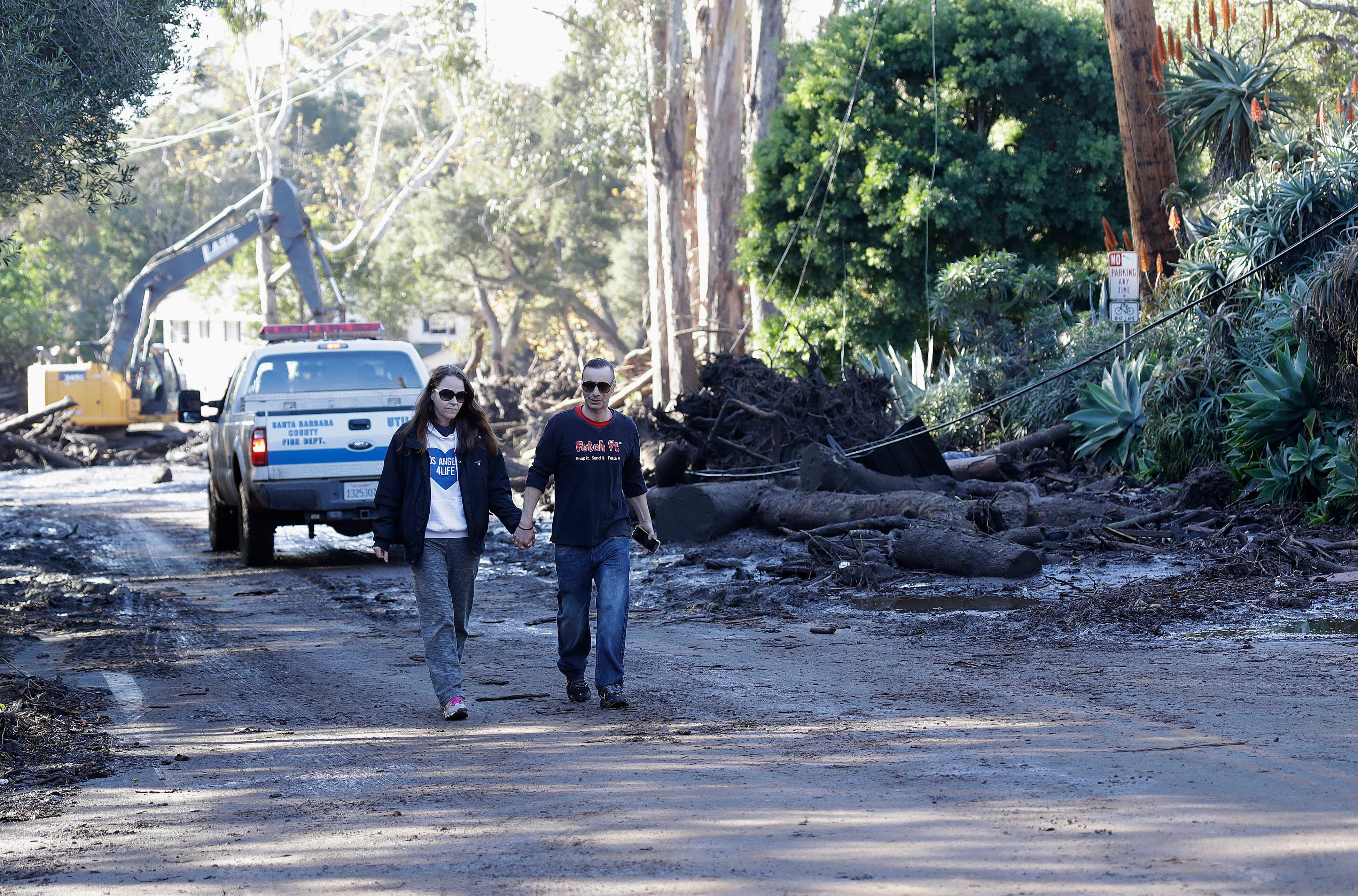 A woman and man walk along a road damaged by storms in Montecito, Calif., Wednesday, Jan. 10, 2018. Dozens of homes were swept away or heavily damaged and several people were killed Tuesday as downpours sent mud and boulders roaring down hills stripped of vegetation by a gigantic wildfire that raged in Southern California last month. (AP Photo/Marcio Jose Sanchez)