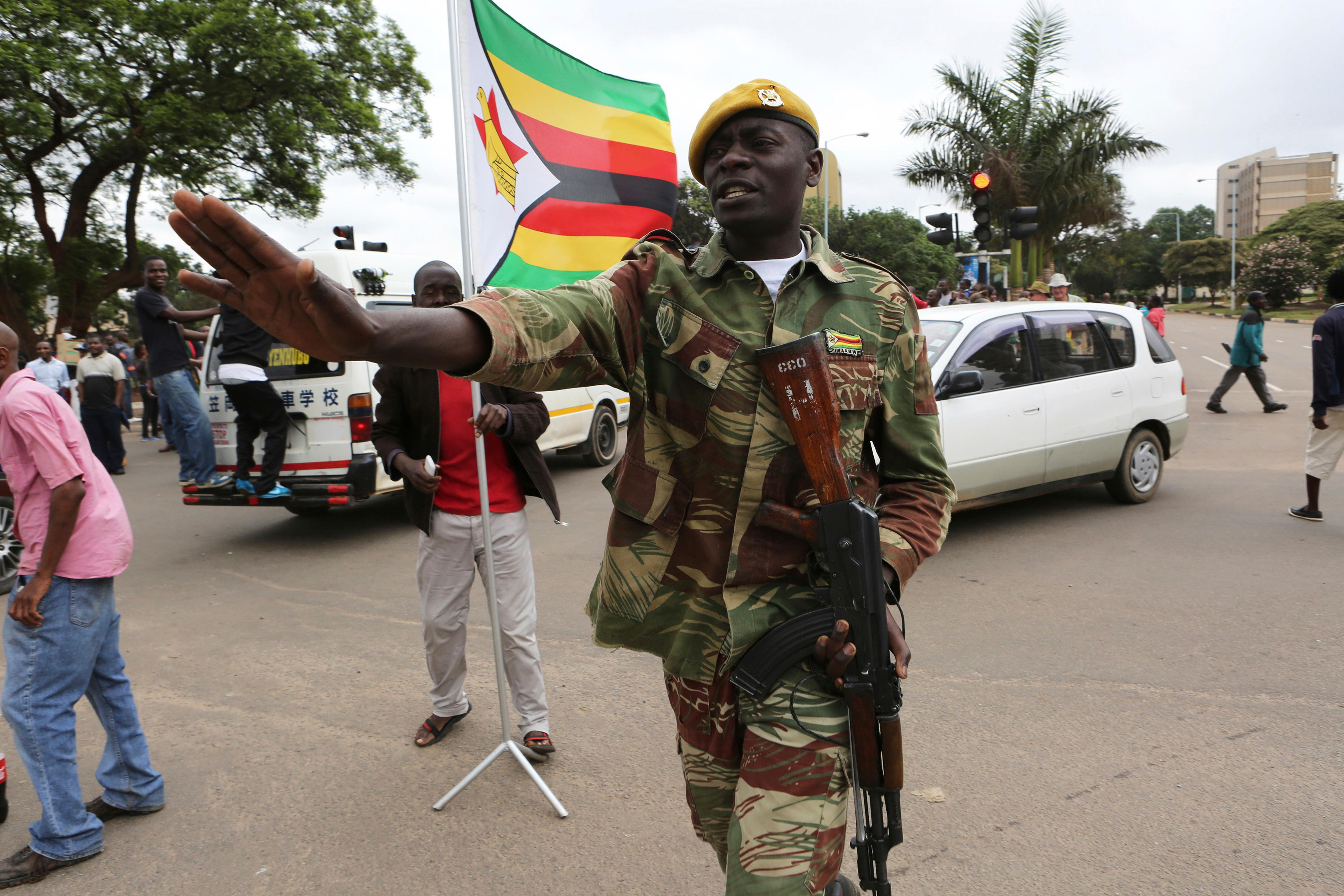 Armed soldiers control traffic as euphoric crowds march on the streets Saturday, Nov. 18, 2017, in Harare, Zimbabwe, demanding the departure of President Robert Mugabe. Zimbabweans giddy with joy raced through intersections, raising their arms in triumph. (AP Photo/Tsvangirayi Mukwazhi)