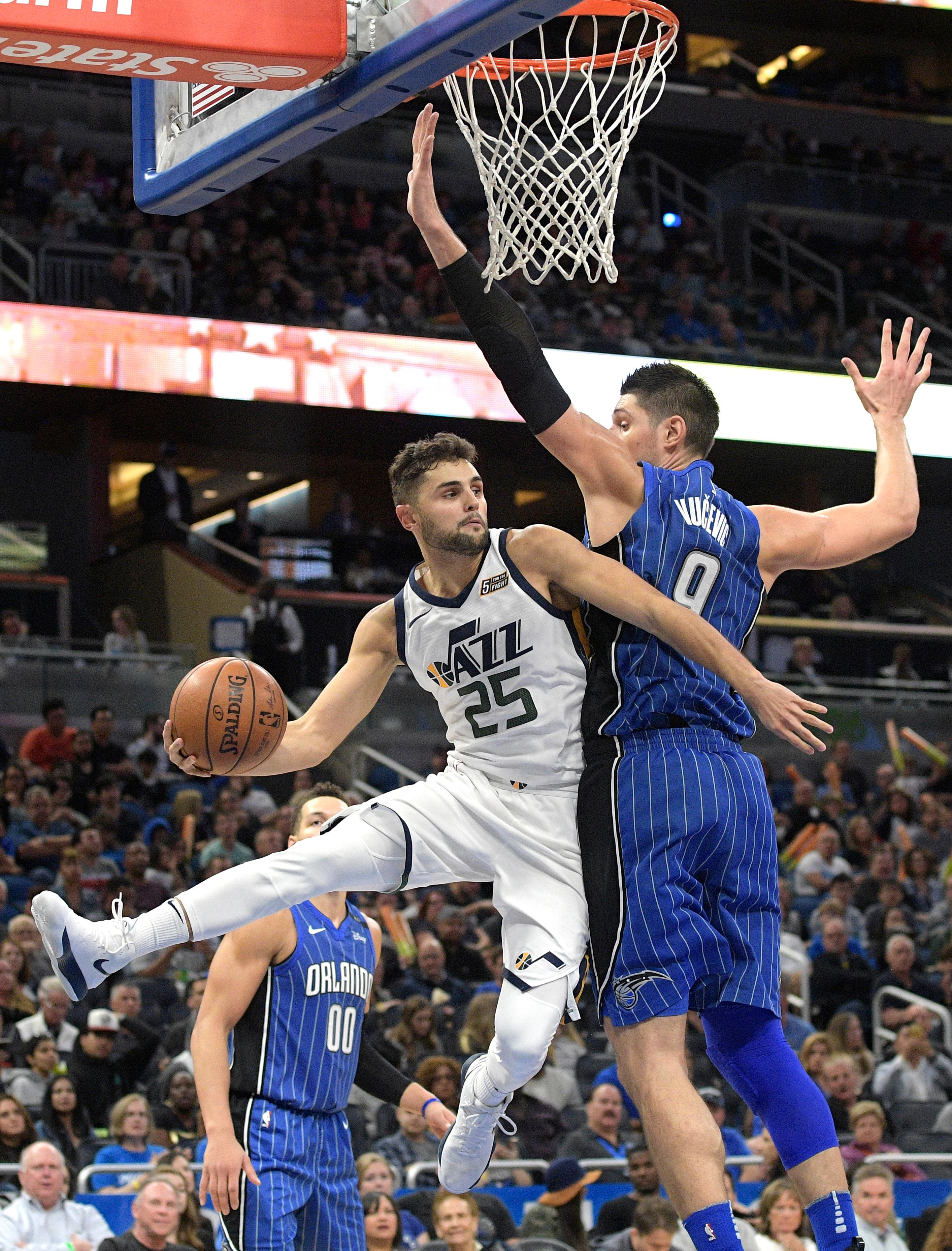 Utah Jazz guard Raul Neto (25) passes the ball around Orlando Magic center Nikola Vucevic (9) after driving to the basket during the second half of an NBA basketball game, Saturday, Nov. 18, 2017, in Orlando, Fla. The Jazz won 125-85. (AP Photo/Phelan M. Ebenhack)