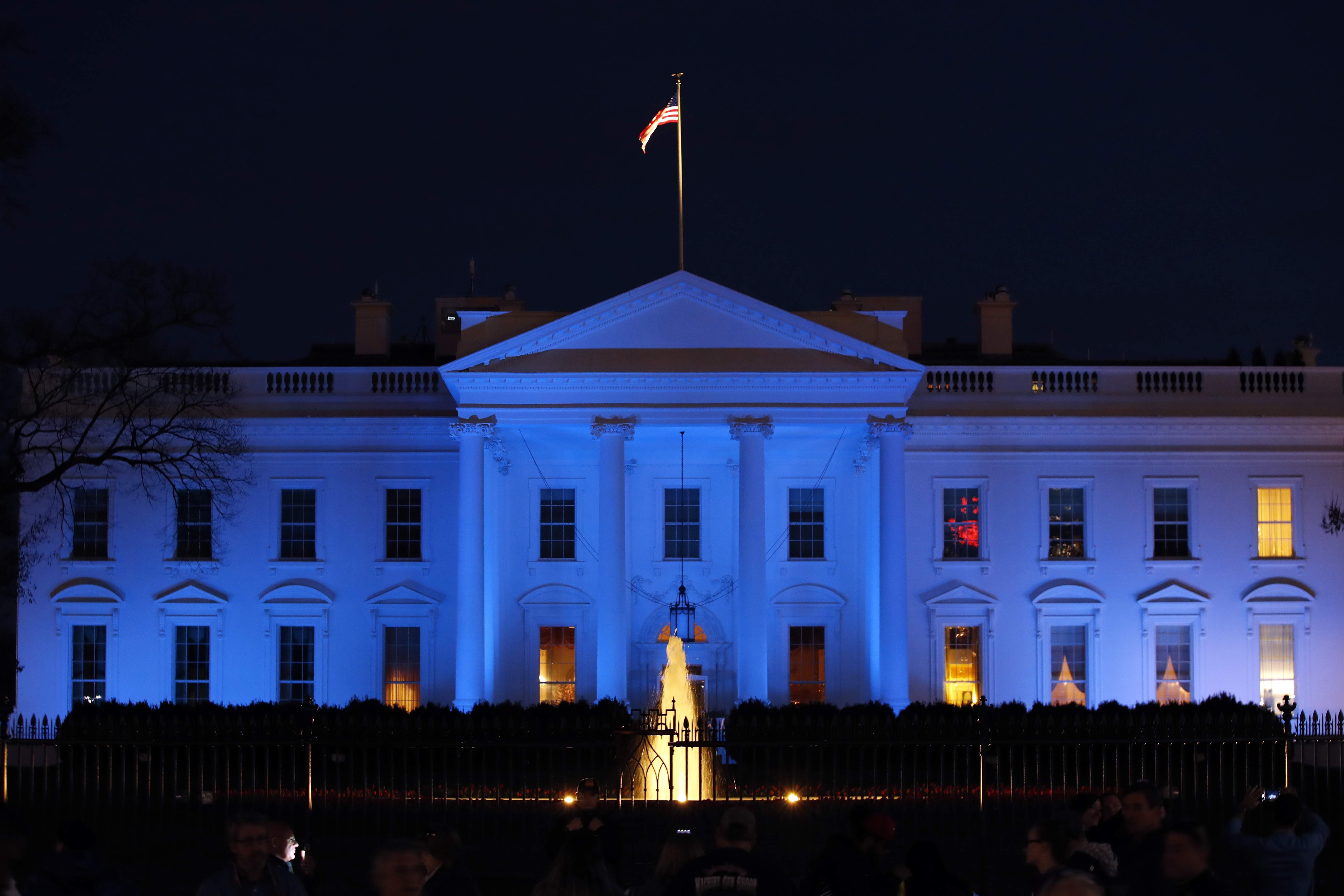 DAY 73 - In this April 2, 2017, file photo, the White House is lit with blue lights in honor of World Autism Awareness Day in Washington. The president was in Washington on day 73, but had no events on his schedule and was not photographed. (AP Photo/Alex Brandon, File)