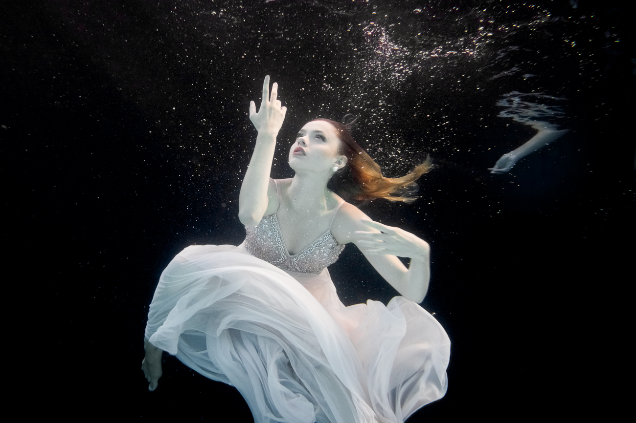 "Statement from artist Tina Gutierrez: ""In this underwater series, a watery environment invites the dancers to yield to the embrace of liquid instead of the greater forces of gravity that they normally experience. The added difficulty of working in the water creates a world of unexpected challenges for the dancer and the photographer. These images are only viewable from below the water and are so fleeting that they can only be captured by the speed of the camera. Due to its calmness yet danger, the water for me has always been a place of peace and solace yet also extreme awareness. The need to make these images is beyond explanation, perhaps as I believe the end result appeals to a deep primal elemental need. Most of the dancers are from the Cincinnati Ballet."" / Model: Isabelle Bohnert Krueger / Makeup: Stefani Carol / Image: Tina Gutierrez // Published: 3.28.20<br><p></p>"