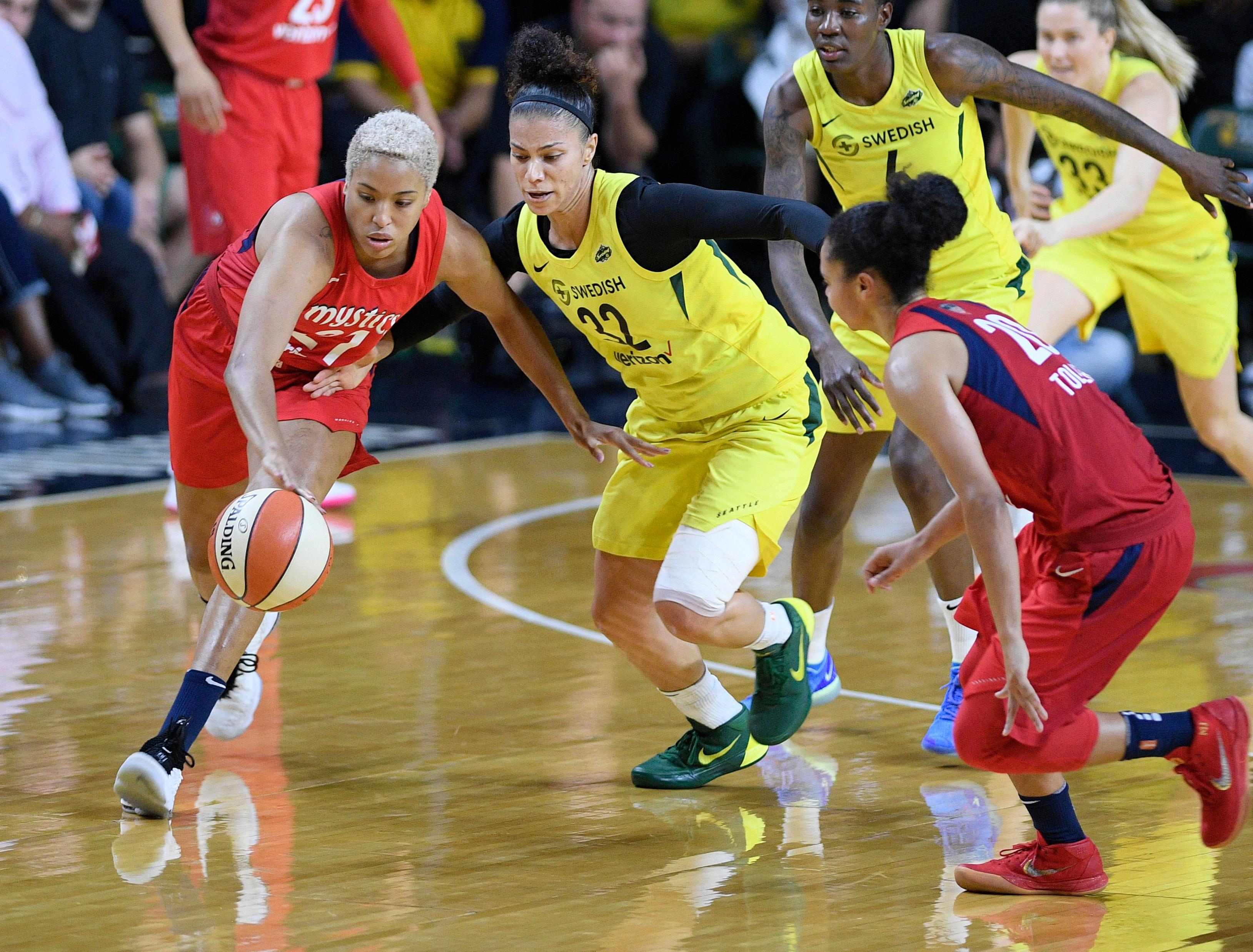 Washington Mystics forward Tianna Hawkins (21) battles for the ball against Seattle Storm forward Alysha Clark (32) during the first half of Game 3 of the WNBA basketball finals, Wednesday, Sept. 12, 2018, in Fairfax, Va. Also seen is Mystics guard Kristi Toliver, right. (AP Photo/Nick Wass)