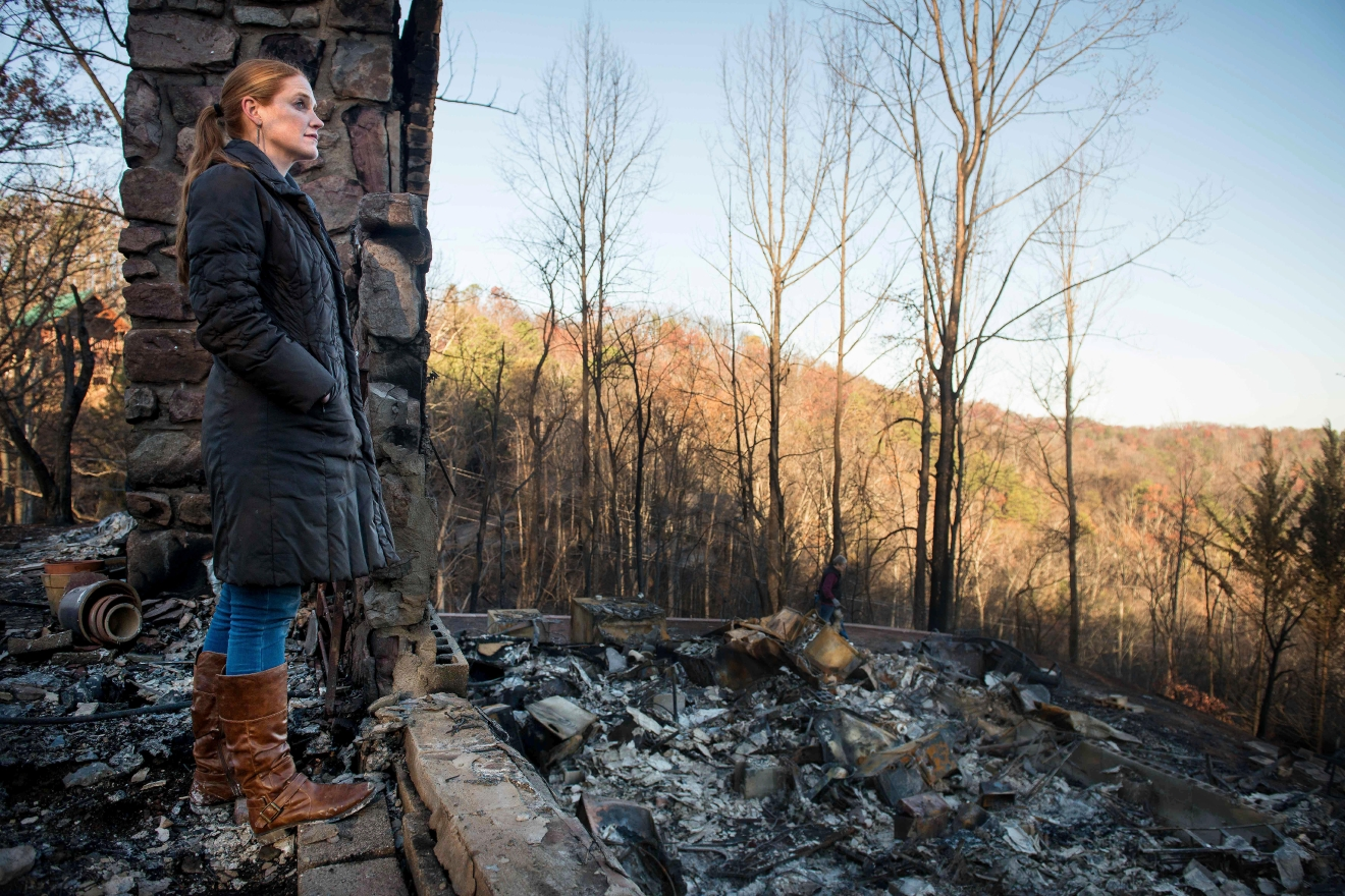 Veronica Carney looks at the skyline from the remains of the home she grew up in, Thursday, Dec. 1, 2016, in Gatlinburg, Tenn. Carney flew in from Massachusetts to assist her parents, Richard T. Ramsey and Sue Ramsey who safely evacuated as a wildfire approached Monday evening. (Andrew Nelles/The Tennessean via AP)