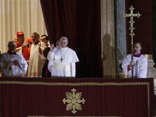 Pope Francis flanked by Monsignor Guido Marini, master of liturgical ceremonies, waves to the crowd from the central balcony of St. Peter's Basilica at the Vatican.